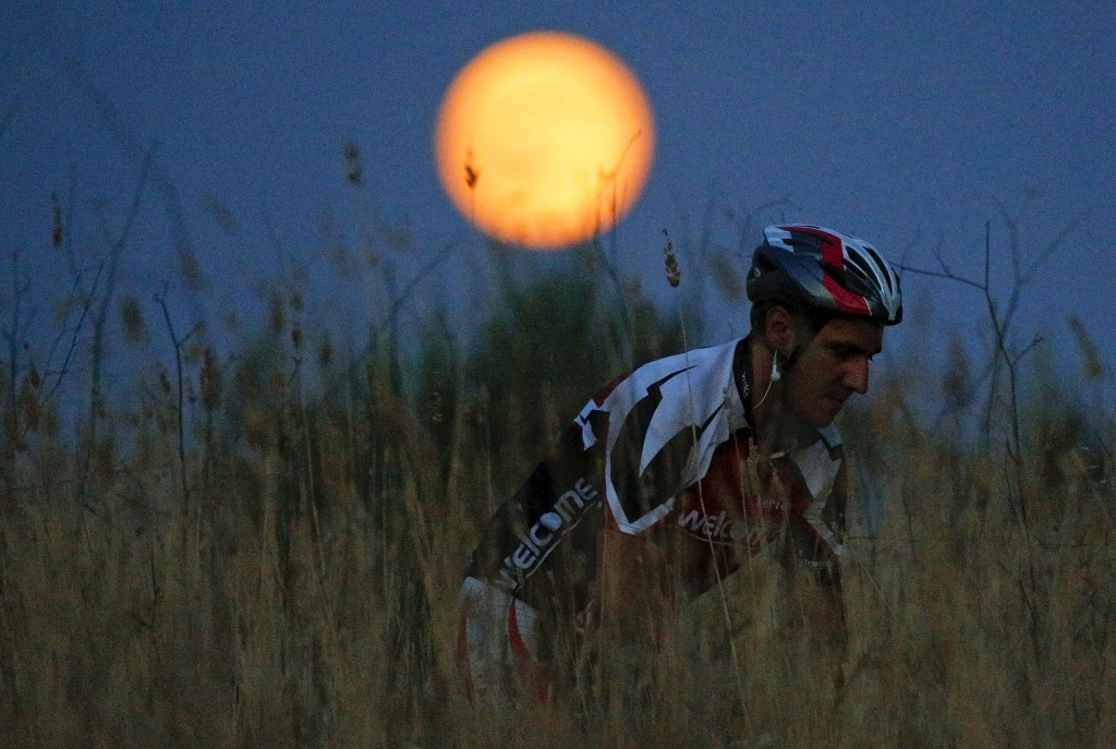 A cyclist rides his mountain bike as the Blue Moon, rises in a park in Rome, Italy, July 31, 2015. Photo by Max Rossi/Reuters.
