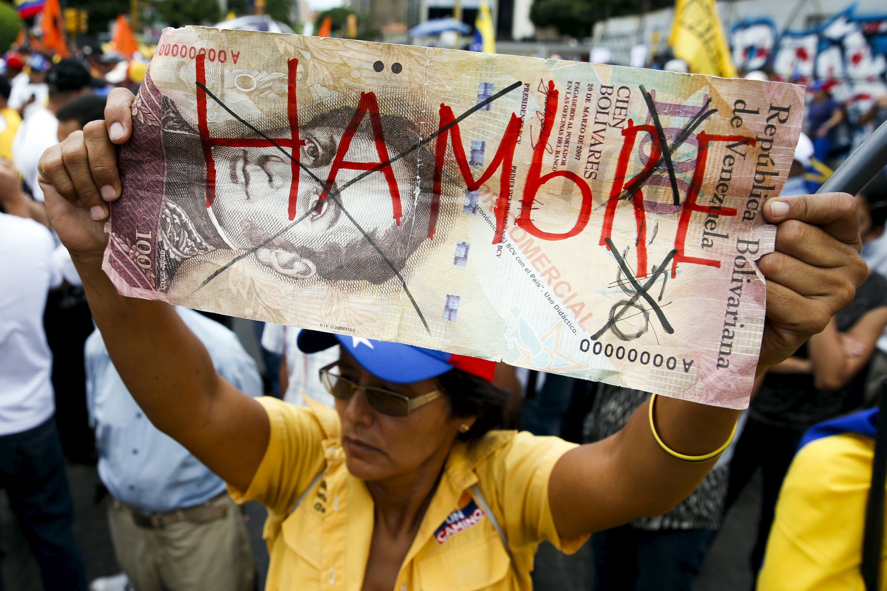 "A woman holds up a giant hundred Bolivar note with the word, ""Hungry"" written on it in Spanish during a gathering to protest the government of President Nicolas Maduro, as well as economic insecurity and shortages, in Caracas, Venezuela, August 8, 2015. Photo by Carlos Garcia Rawlins/Reuters"