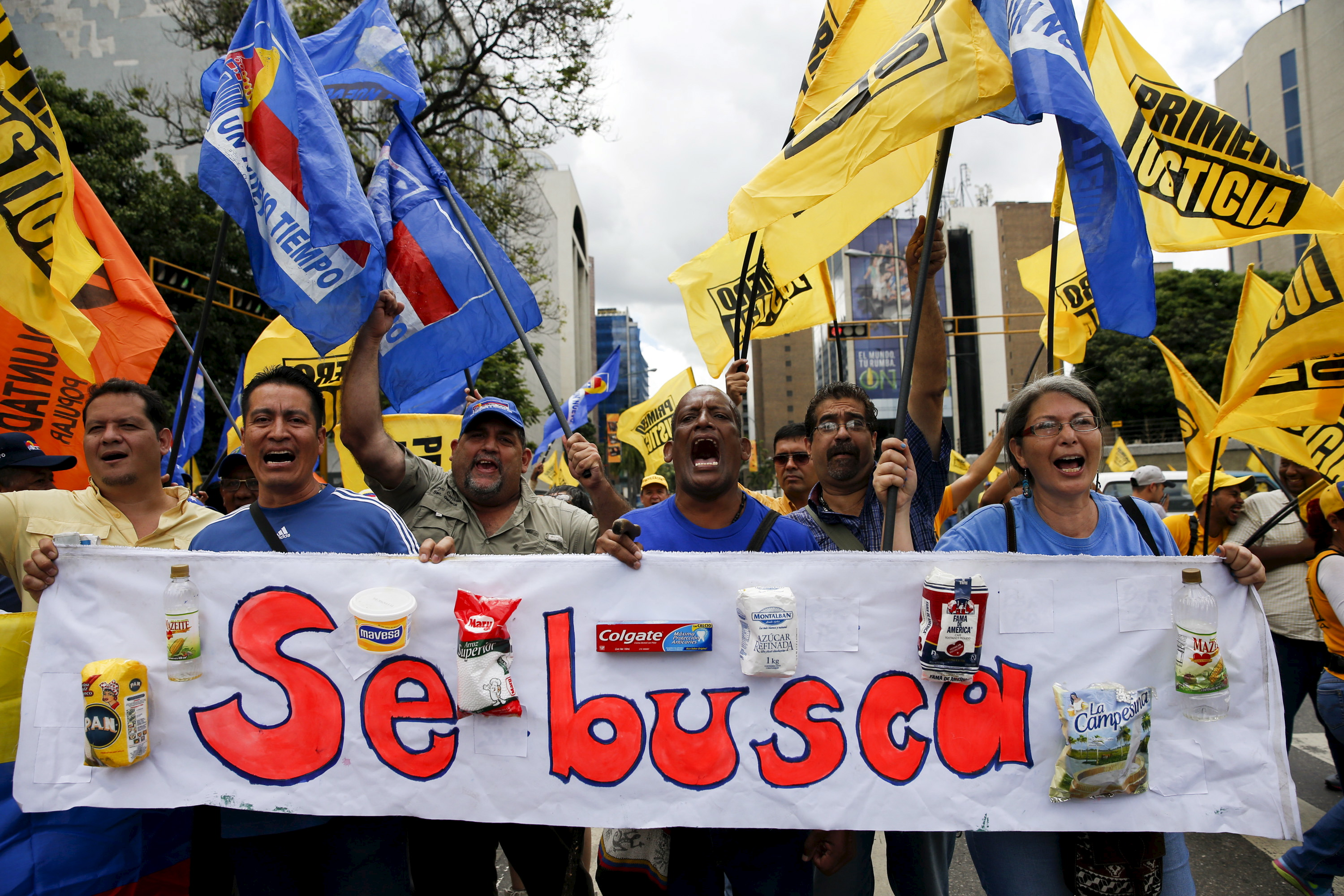 "Venezuelans hold a banner bearing basic household products, that reads, ""Wanted"" in Spanish, while they shout during a gathering to protest the government of President Nicolas Maduro and economic insecurity and shortages, in Caracas, Venezuela, August 8, 2015. Venezuelan supermarkets are increasingly being targeted by looters as swollen lines and prolonged food shortages spark frustration in the OPEC nation struggling with an economic crisis. Photo by Carlos Garcia Rawlins"