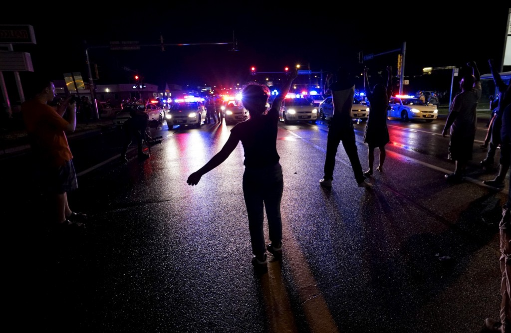 A protester yells at a police line shortly before shots were fired in a police-officer involved shooting in Ferguson, Missouri.  Two people were shot in the midst of a late-night confrontation between riot police and protesters, after a day of peaceful events commemorating the fatal shooting of Michael Brown by a white officer one year ago.  REUTERS/Rick Wilking - RTX1NPUQ