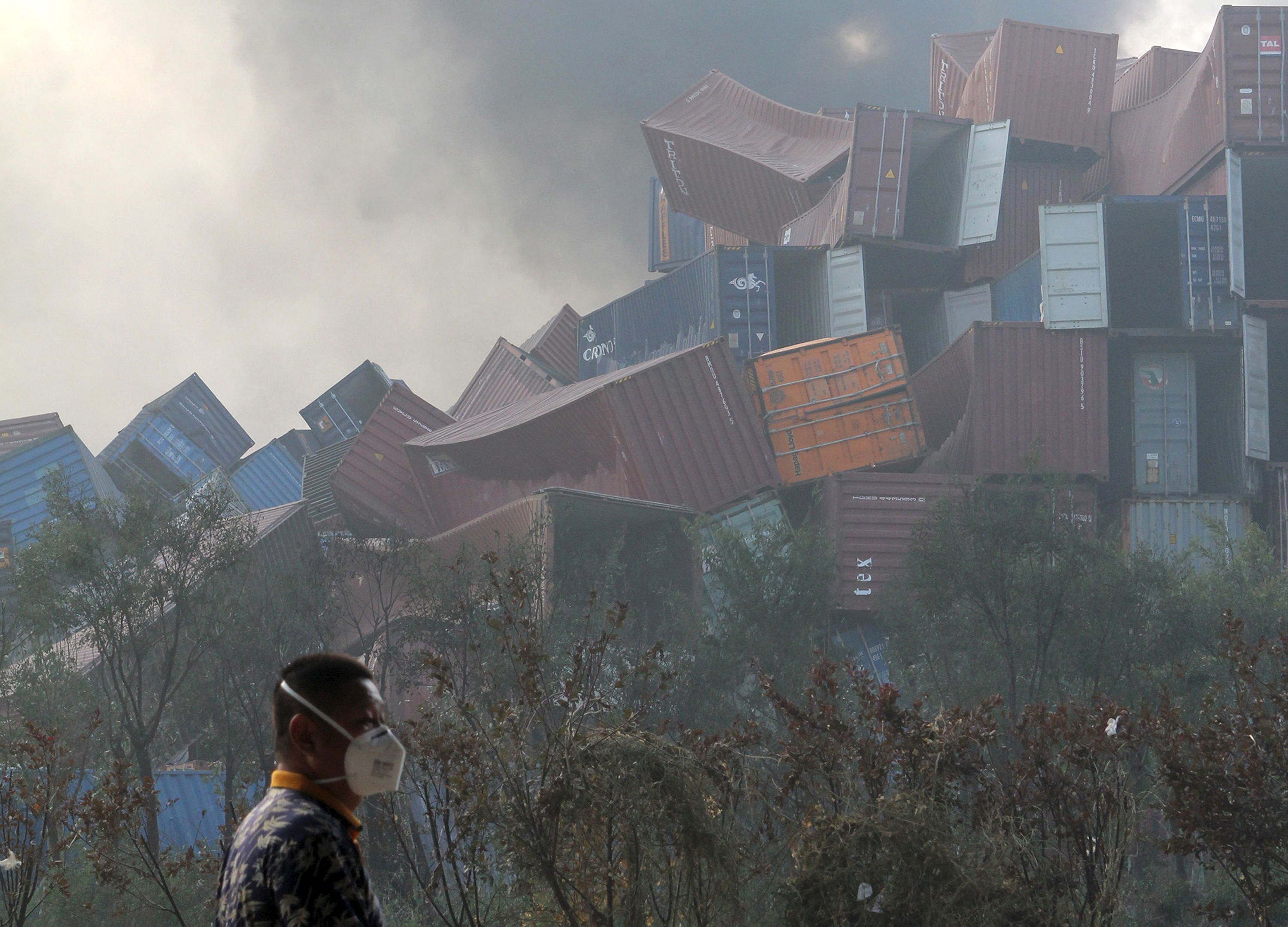 A man wearing a mask walks past overturned shipping containers near the scene of the explosions. Photo by Reuters