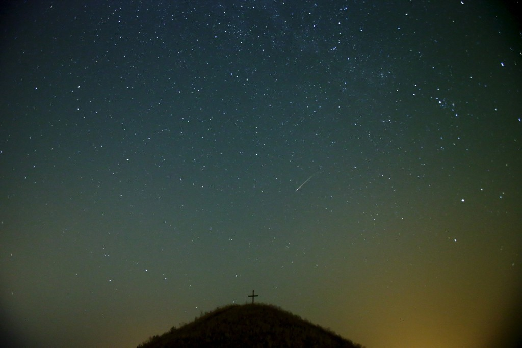 A meteor streaks across the sky over Leeberg hill during the Perseid meteor shower near Grossmugl in the early morning of August 13, 2015. Photo by Peter Bader/Reuters