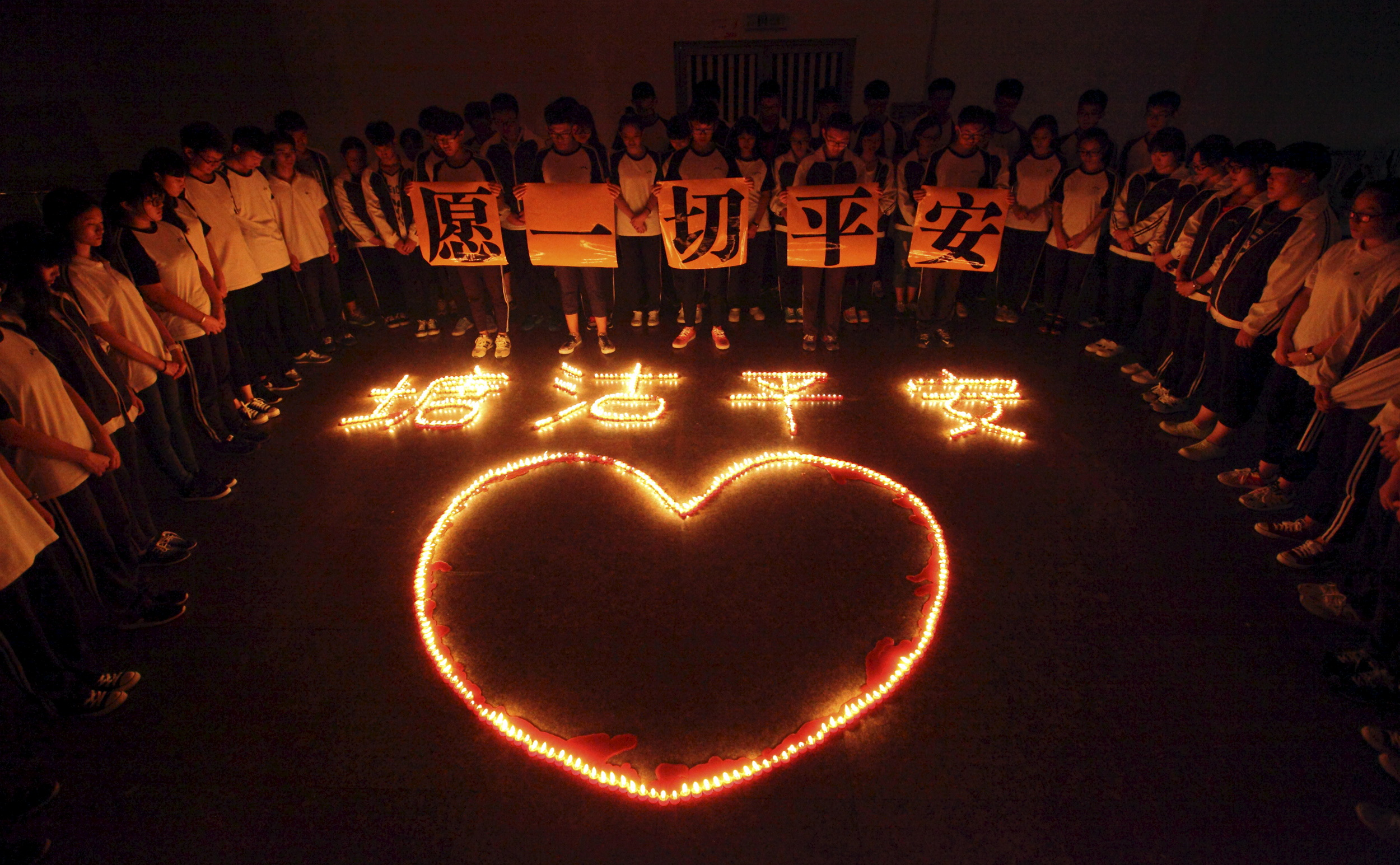 "Students and teachers stand around lighted candles which form into Chinese characters ""Tanggu be safe"" and a heart shape, during a candlelight vigil for victims of the explosions at a school in Zhuji, Zhejiang province, China, August 13, 2015. Tanggu is a name for the affected portion of Tianjin. Photo by Reuters"