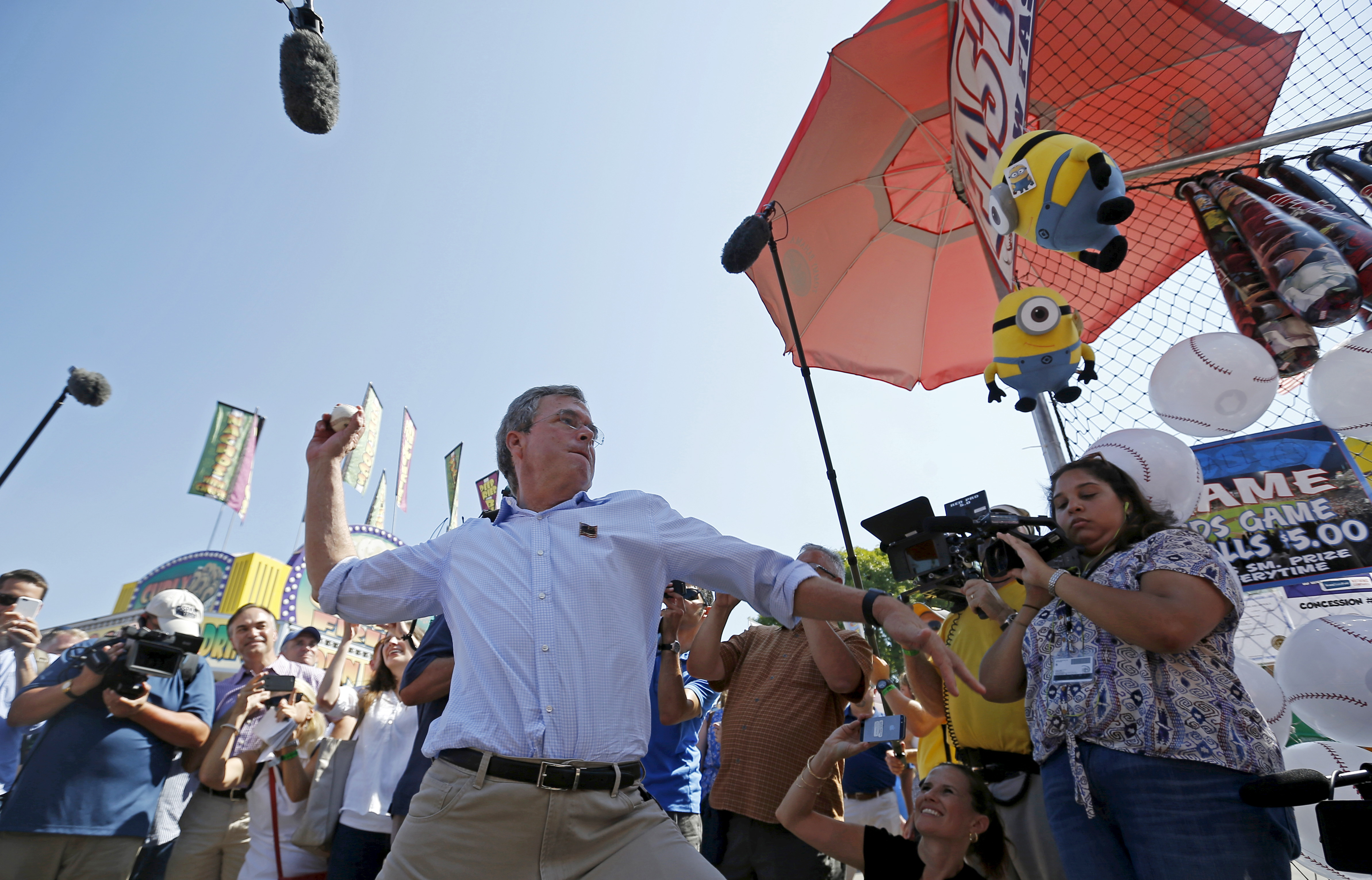 U.S. Republican presidential candidate Jeb Bush throws a baseball as he campaigns at the Iowa State Fair in Des Moines, Iowa, United States, August 14, 2015. REUTERS/Jim Young   - RTX1OBCX