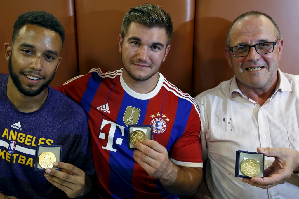 (L-R) Three men who helped to disarm an attacker on a train from Amsterdam to France, Anthony Sadler, from Pittsburg, California, Aleck Sharlatos from Roseburg, Oregon, and Chris Norman, a British man living in France, pose with medals they received for their bravery at a restaurant in Arras, France August 22, 2015. A machine gun-toting attacker wounded three people on a high-speed train in France on Friday before being overpowered by passengers who included an American soldier. The wounded were the soldier, French actor Jean-Hugues Anglade, and a Briton. Local media reported that U.S. Marines were among those who brought down the gunman. Officials said the attacker was arrested after the shooting when the Amsterdam to Paris train stopped at Arras station in northern France.  REUTERS/Pascal Rossignol  - RTX1P67M