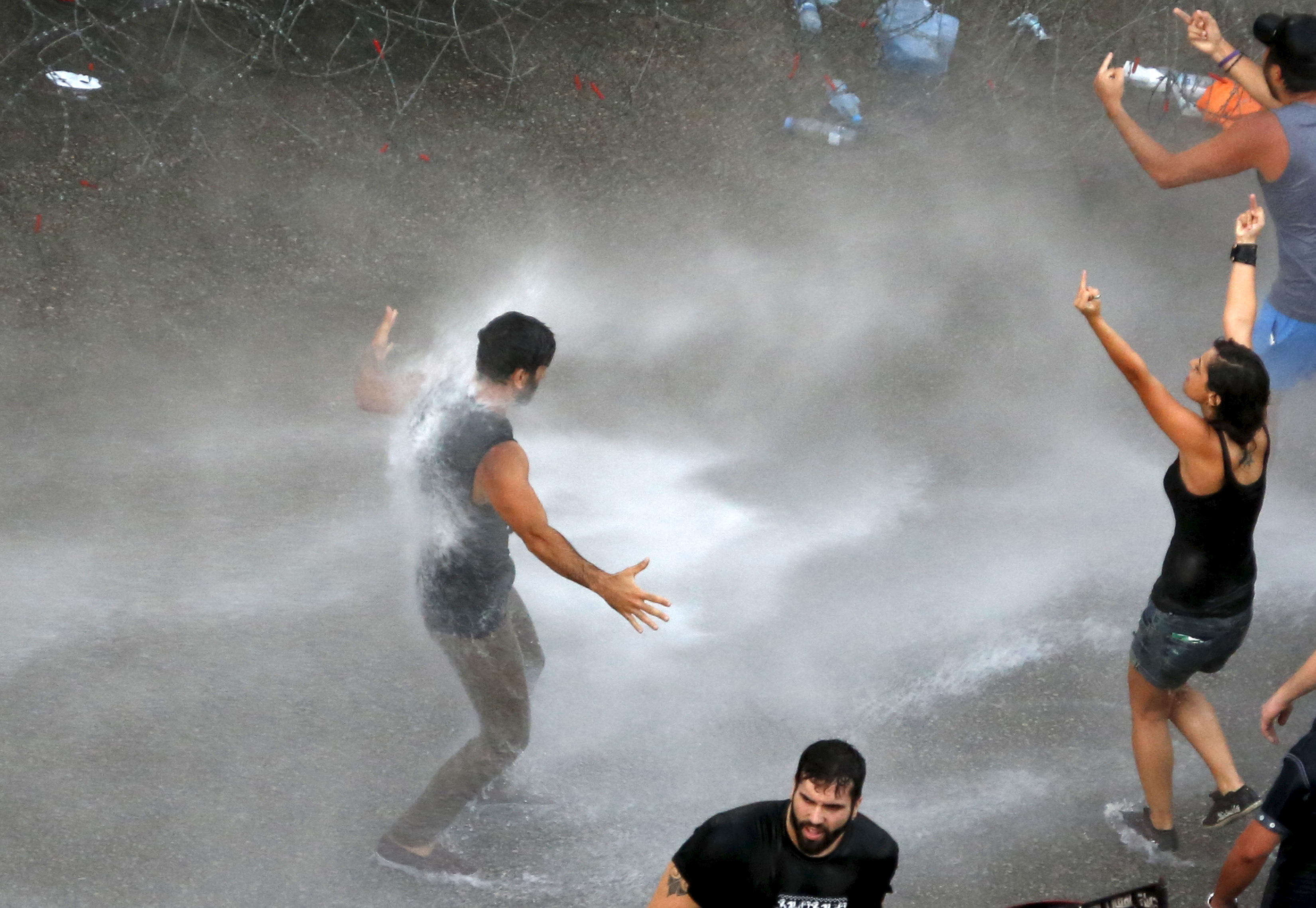 Lebanese protesters are sprayed with water during a demonstration against corruption and garbage collection problems near the government palace in Beirut on Aug. 22. Photo by Jamal Saidi/Reuters