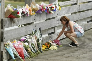 A woman lays flowers near to the site where a Hawker Hunter fighter jet crashed onto the A27 road at Shoreham near Brighton, Britain August 23, 2015. Photo by Luke MacGregor/Reuters.