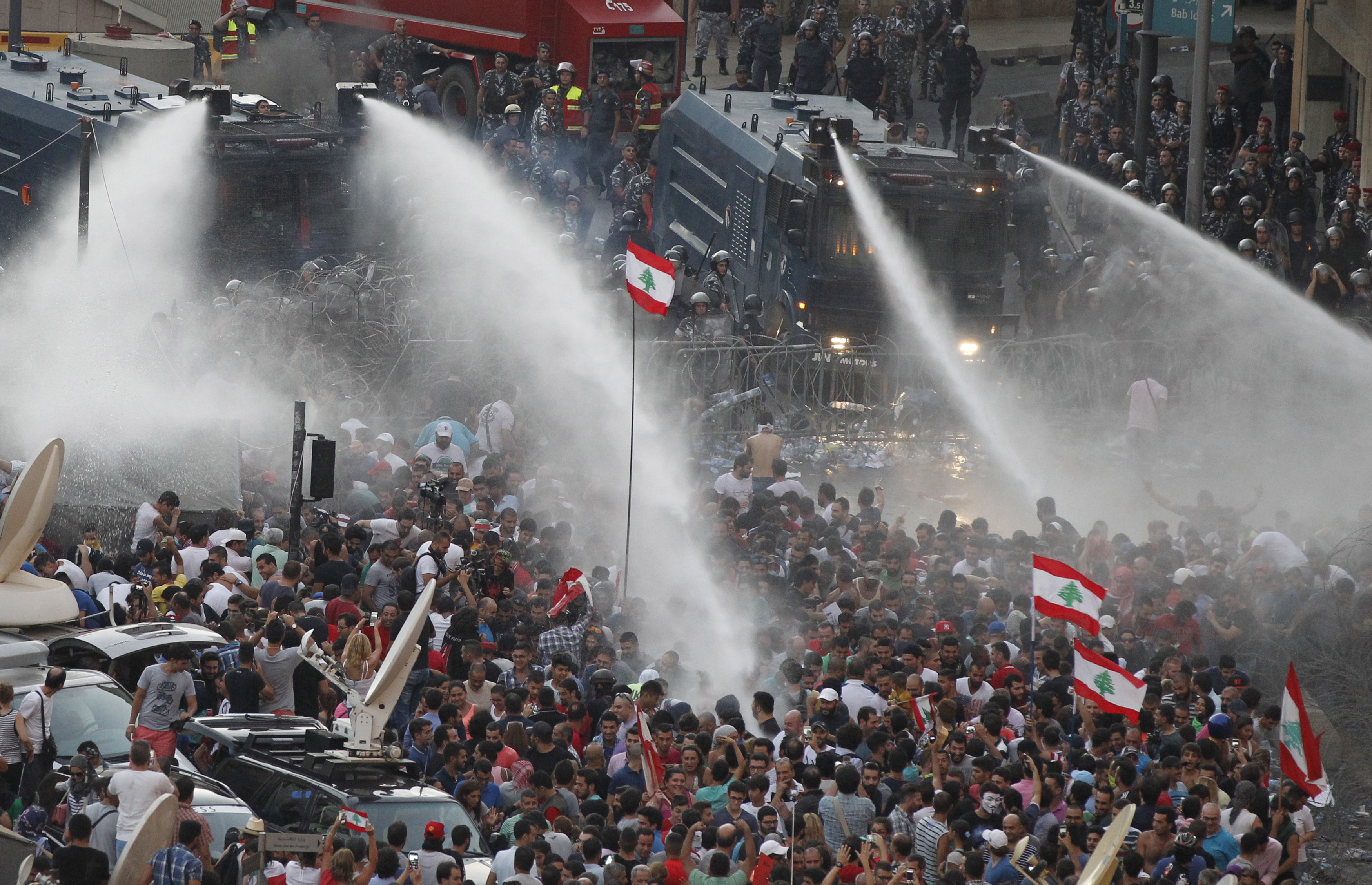 Lebanese protesters are sprayed with water during a demonstration against the government near Prime Minister Tammam Salam's offices in Beirut on Aug. 23. Photo by Mohamed Azakir/Reuters