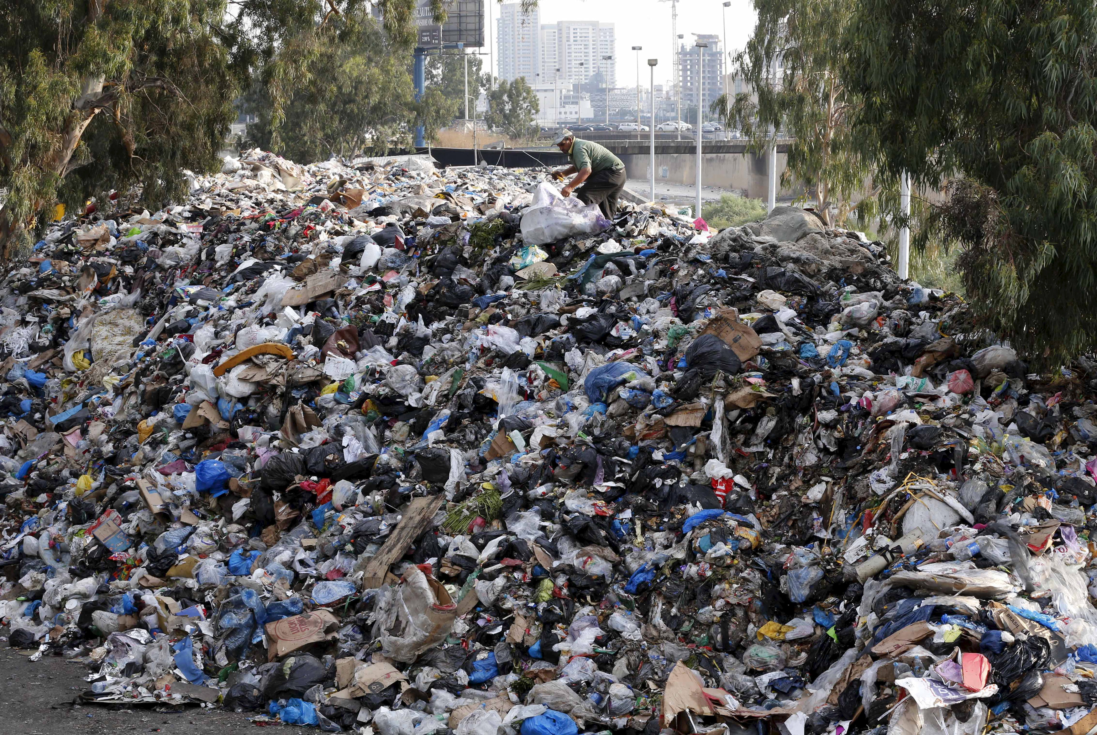 A man sifts through garbage piled on the bank of the Beirut River in Lebanon on Aug. 24. Photo by Mohamed Azakir/Reuters