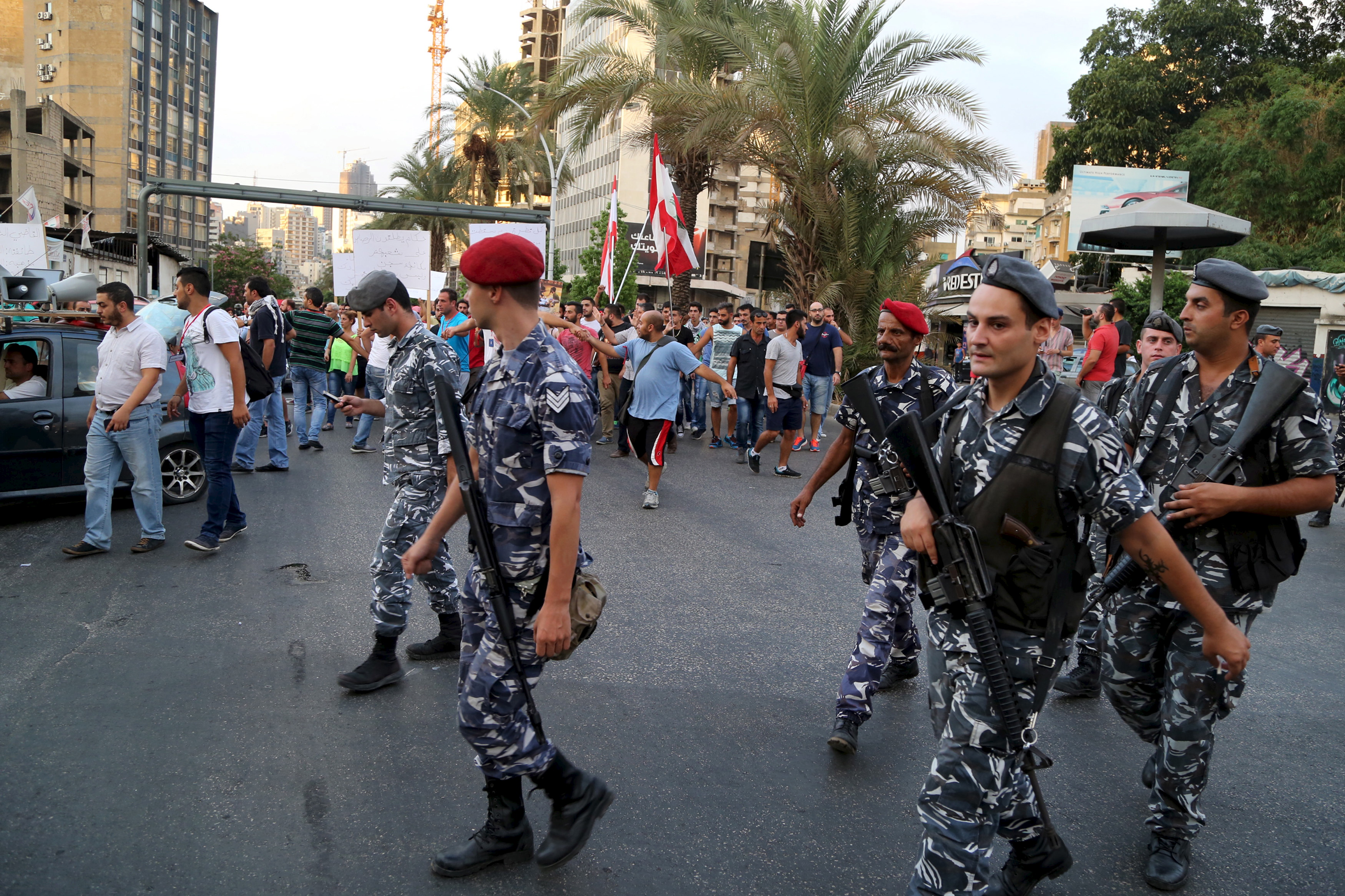 Members of Lebanon's security services escort demonstrators marching toward the government building in Beirut on Aug. 24. Several hundred Lebanese protesters chanted anti-government slogans as they marched on Monday after two days of much larger rallies that descended into violence. Photo by Aziz Taher/Reuters