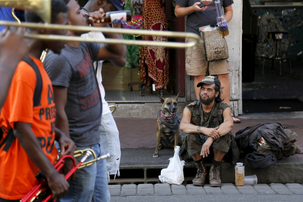 A man and his dog watch a brass band perform on Bourbon Street one day before the ten year anniversary of Hurricane Katrina in New Orleans, Louisiana, August 28, 2015. REUTERS/Jonathan Bachman - RTX1Q4B3