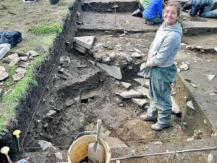 University of Pittsburgh student Tori Maatta stands proudly in front of her find -- a stone drain running parallel to an interior wall. Photo courtesy Tori Maatta.