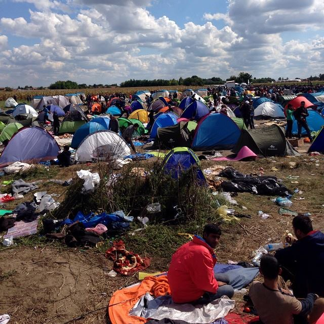 "This overflow refugee camp outside of Roszke, Hungary -- a huge sprawling field -- has become ""home"" to the hundreds of refugees who can't fit into the ""official"" camp a 1/2 mile away. A thick phalanx of Hungarian police box the crowd in. Several hundred people broke free of the police on Monday Tuesday to walk to Budapestm but were reportedly caught and bussed back. Photo by William Brangham."