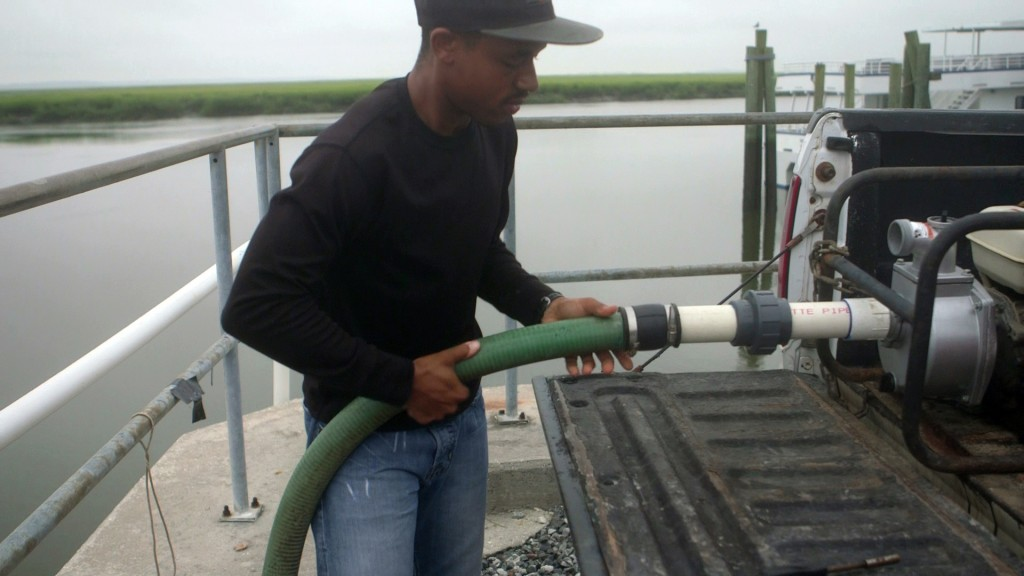 Marine technician Dontrece Smith pumps seawater from Dolby Sound, Georgia. Photo by Mike Fritz