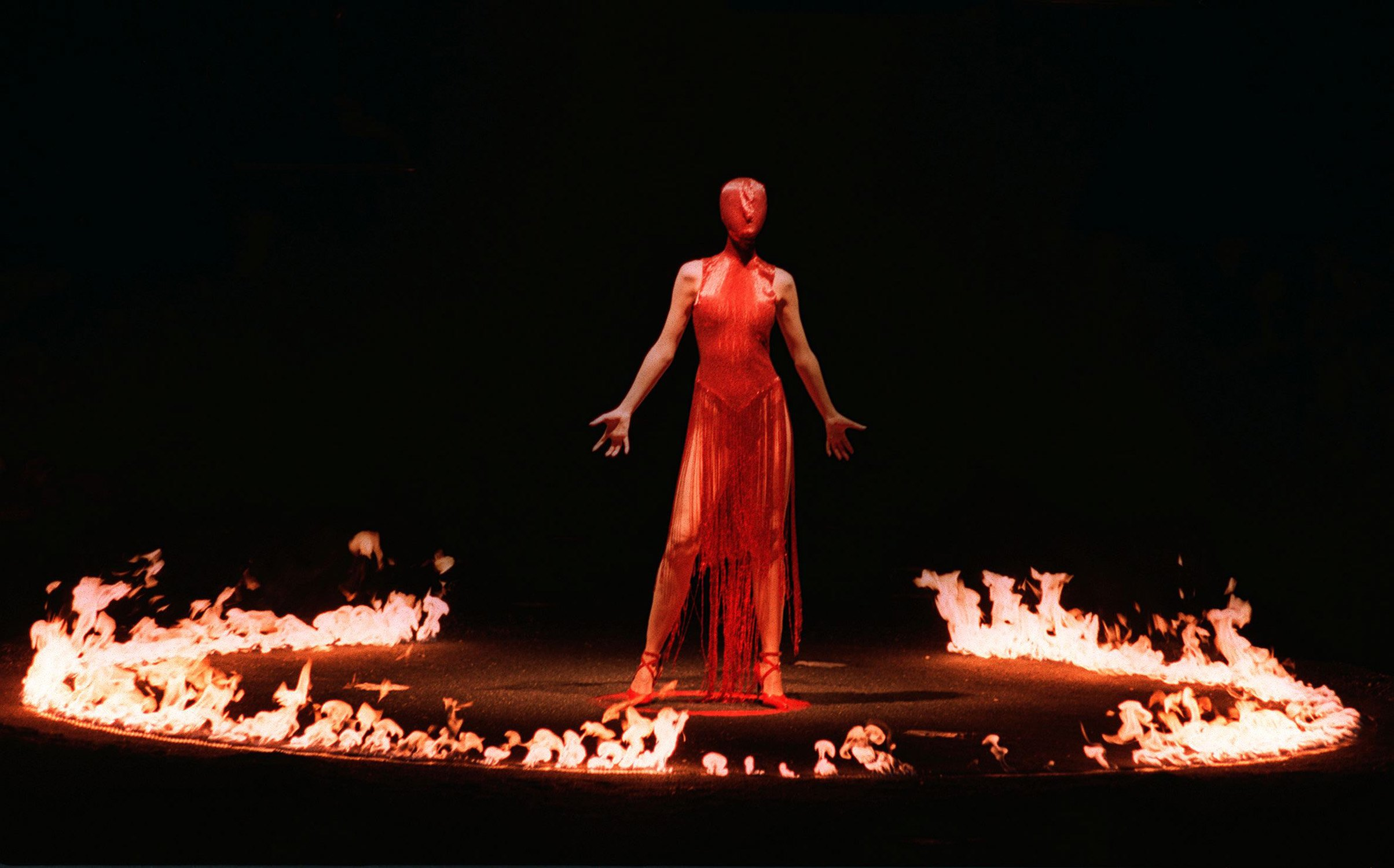 A model wearing a red hooded cat suit, stands among a ring of fire during the finale of British designer Alexander McQueen's autumn/winter 1998/1999 fashion collection on the last day of London Fashion week. Photo by Paul Vicente/AFP/Getty Images