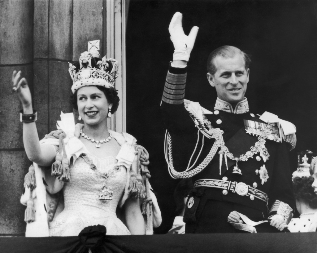 Queen Elizabeth II and the Duke of Edinburgh wave at the crowds from the balcony at Buckingham Palace on June 2, 1953. Photo by Keystone/Getty Images