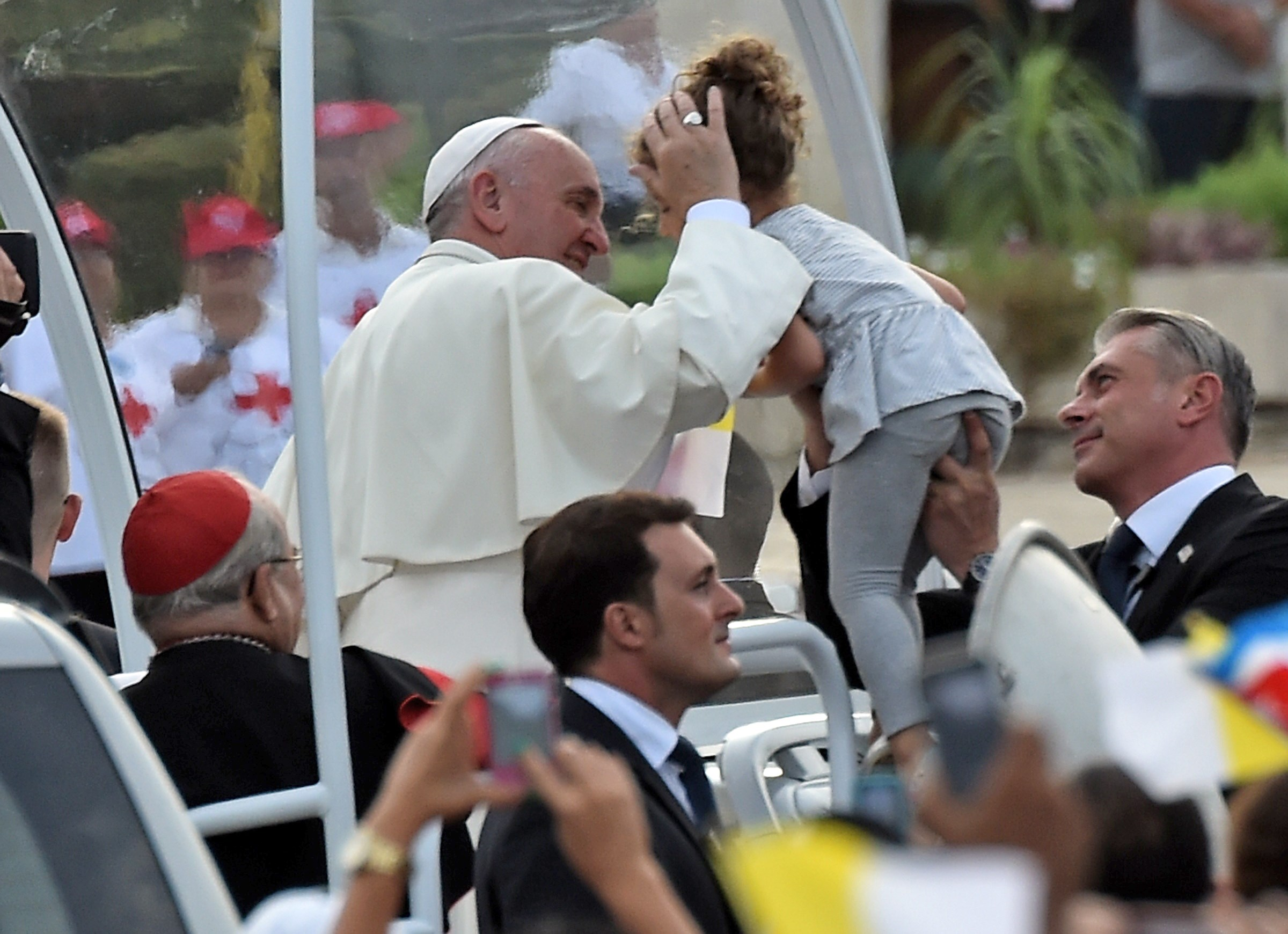 Pope Francis kisses a girl as he arrives at Revolution Square in Havana on September 20, 2015. Pope Francis will give mass on Revolution Square, the biggest event of his trip to Cuba, with nearly a million people expected to attend. The pontiff's eight-day tour will also take him to the United States.   AFP PHOTO / RODRIGO ARANGUA        (Photo credit should read RODRIGO ARANGUA/AFP/Getty Images)