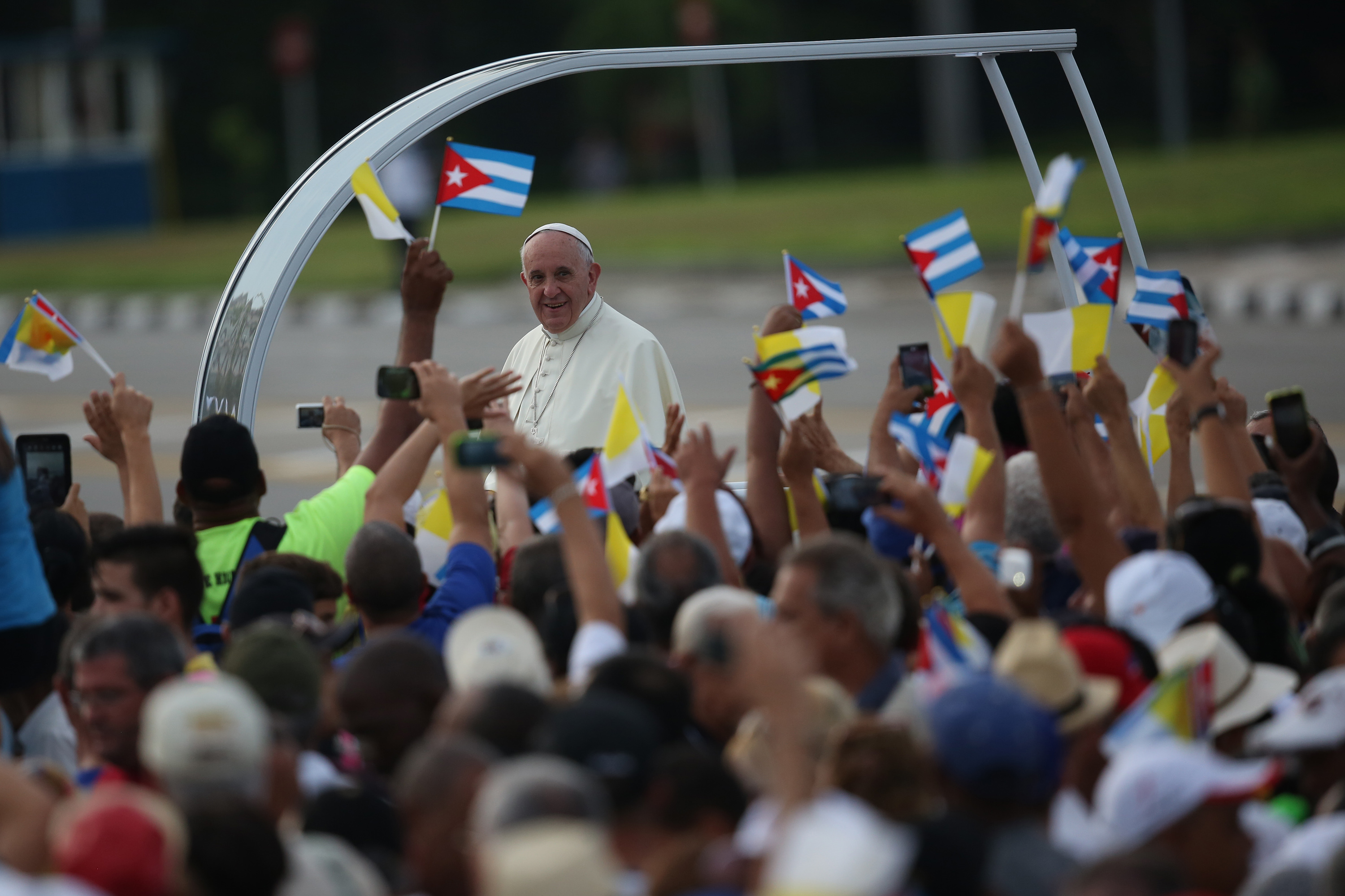 HAVANA, CUBA - SEPTEMBER 20: People wave Cuban and Papal flags as Pope Francis passes by as he arrives to perform Mass on September 20, 2015 in Revolution Square in Havana, Cuba. Pope Francis is on the first full day of his three day visit to Cuba where he will meet President Raul Castro and hold Mass in Revolution Square before travelling to Holguin, Santiago de Cuba and El Cobre then onwards to the United States.  (Photo by Carl Court/Getty Images)