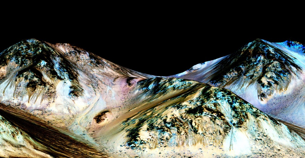 These dark, narrow, 100 meter-long streaks called, recurring slope lineae, flowing downhill on Mars are inferred to have been formed by contemporary flowing water. Planetary scientists have now detected hydrated salts on these slopes at Hale crater, corroborating their original hypothesis that the streaks are indeed formed by liquid water. The blue color seen upslope of the dark streaks are thought not to be related to their formation, but instead are from the presence of the mineral pyroxene. Photo by NASA/JPL/University of Arizona