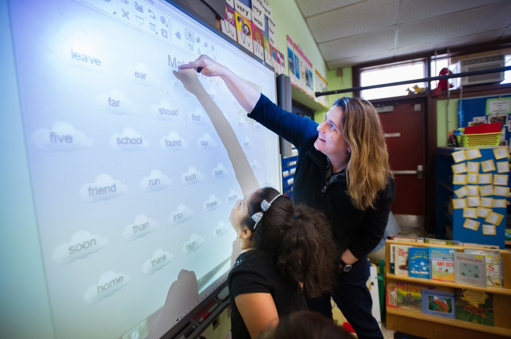 Pleasant View Elementary School  Principal Gara Field works with first grader  Rachael Rodriguez  on a word game on an interactive screen during free time in Rodriguez' class this past May. Photo by Gretchen Ertl/Hechinger Report
