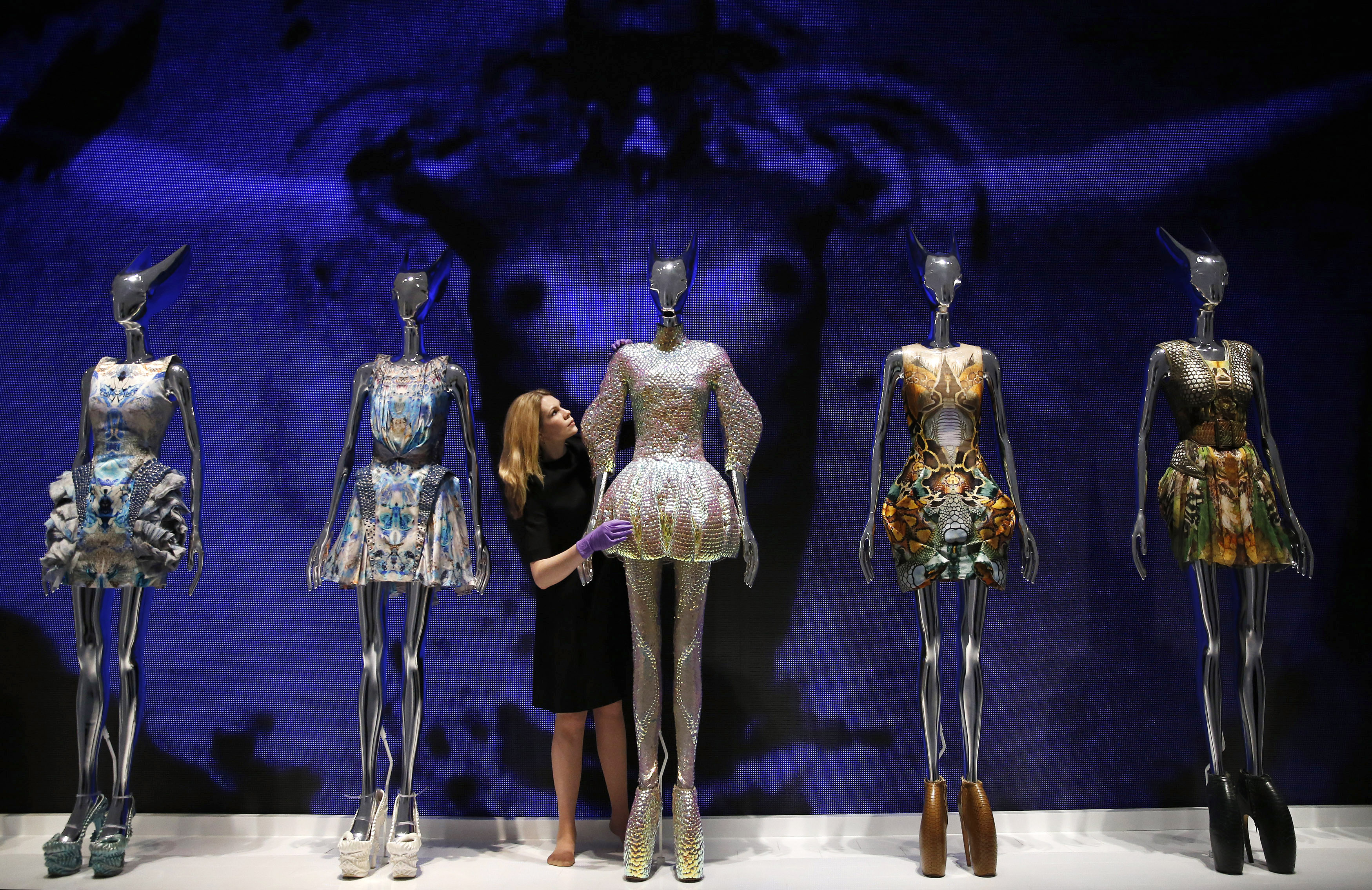 "A staff member amid the dresses from the Alexander McQueen Plato's Atlantis 2010 collection in the ""Alexander McQueen: Savage Beauty"" exhibition in London on March 12, 2015. Photo by Suzanne Plunkett/Reuters"