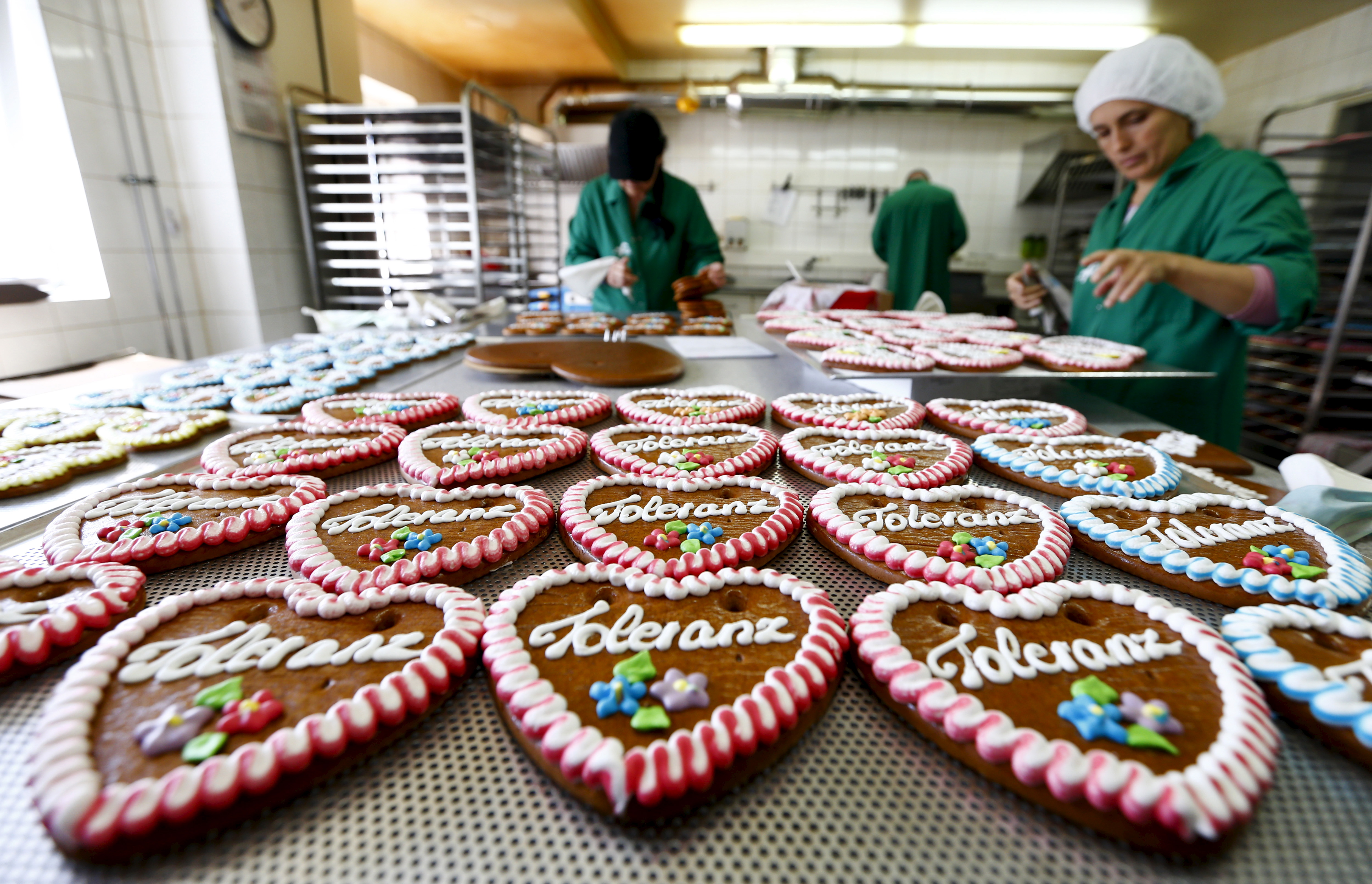 Women decorate gingerbread Oktoberfest hearts with icing at the Fesey company factory in Munich, Germany September 15, 2015. Fesey will produce about 1000 gingerbread hearts with the word 'tolerance' for the upcoming Oktoberfest. The proceeds will go toward the Caritas charity organisation. REUTERS/Michaela Rehle - RTS1861
