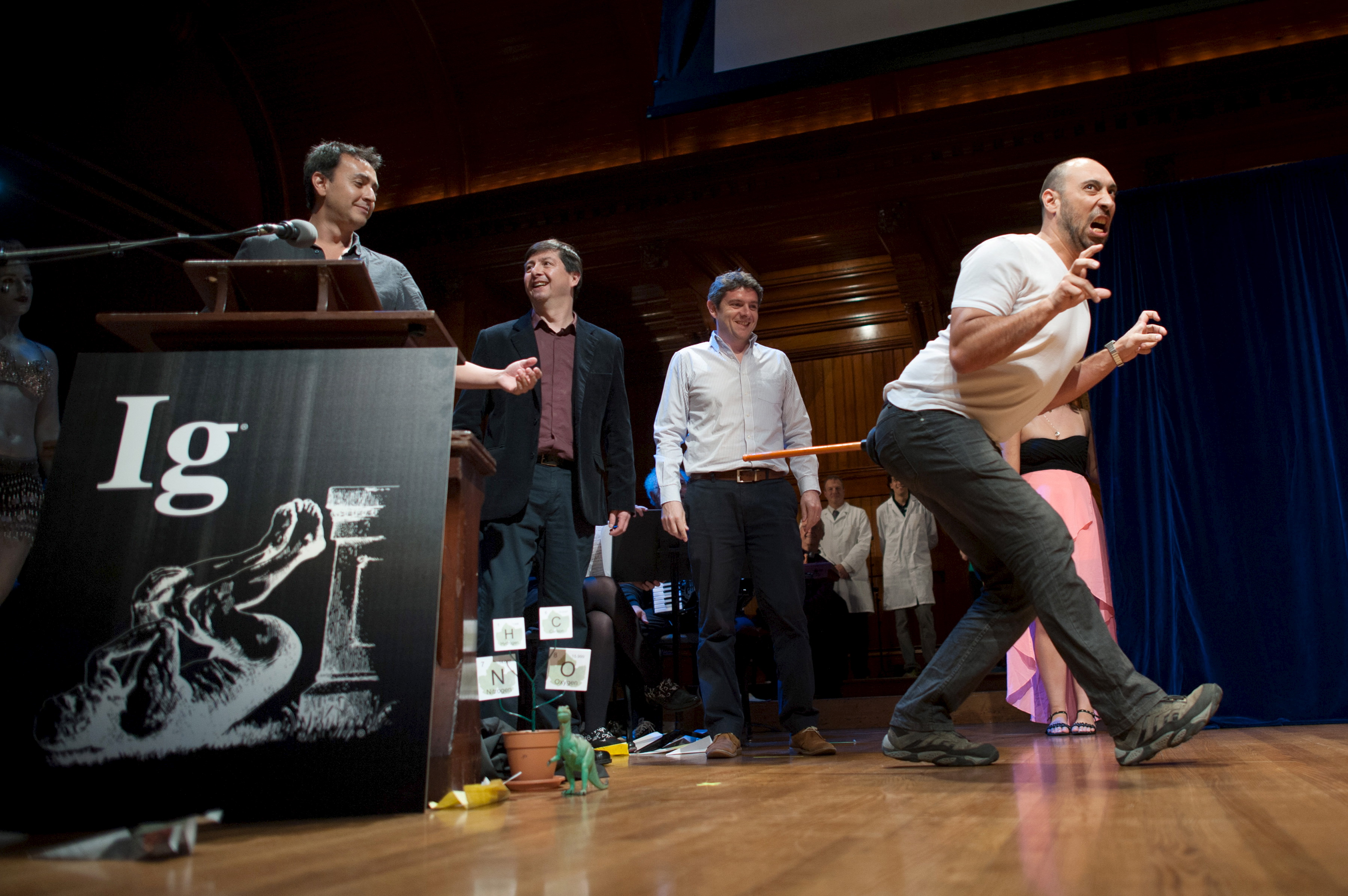 Bruno Grossi (R), walks like a dinosaur as he and his team accept the Ig Nobel Prize in Biology at the 25th First Annual Ig Nobel Prizes awards ceremony at Harvard University in Cambridge, Massachusetts. He and his team observed that when you attach a weighted stick to the rear end of a chicken, it would move in a manner similar to a dinosaur. Photo by Gretchen Ertl/Reuters