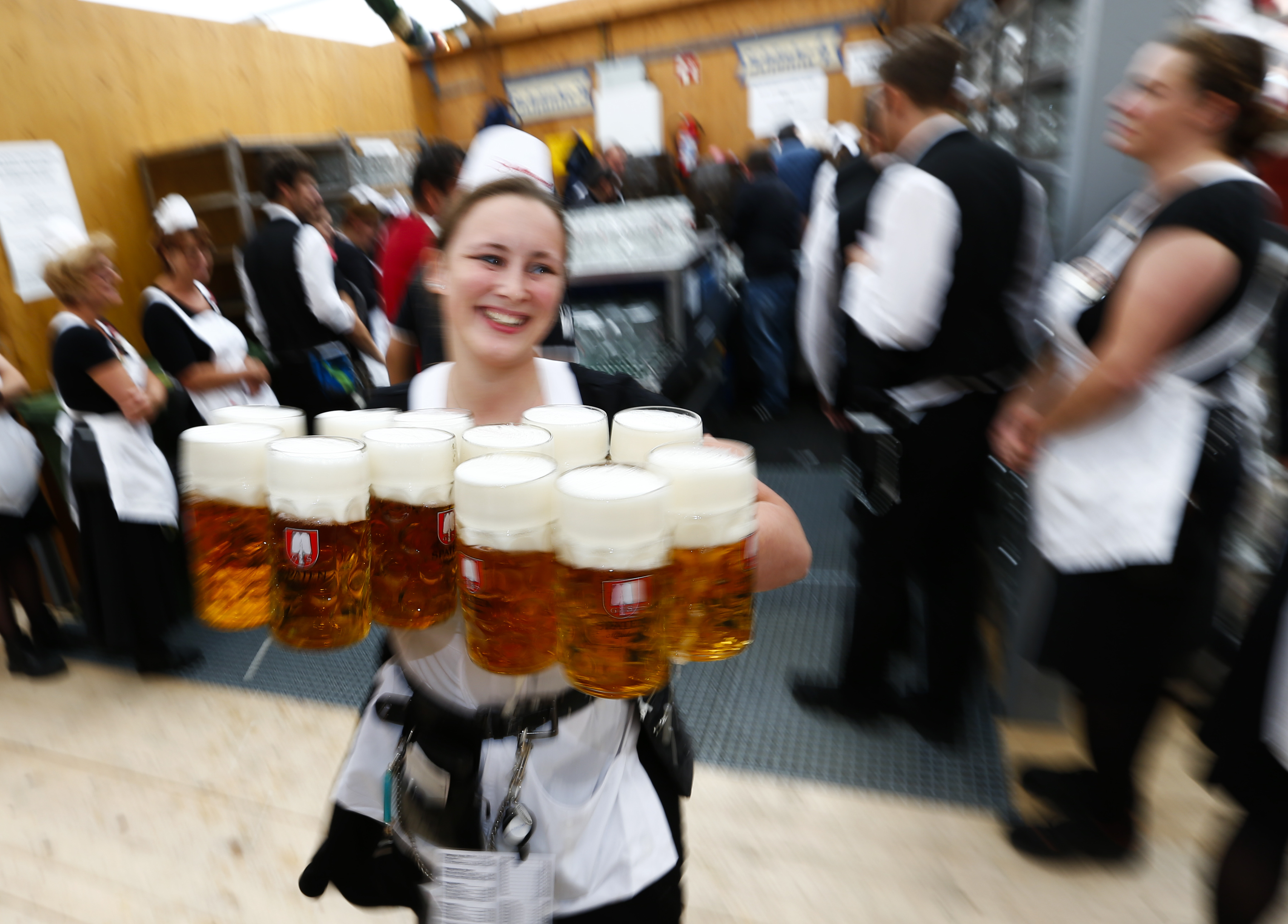 A waitress carries beer in a tent during the 182nd Oktoberfest in Munich, Germany, September 19, 2015. Photo by Michaela Rehle/Reuters.