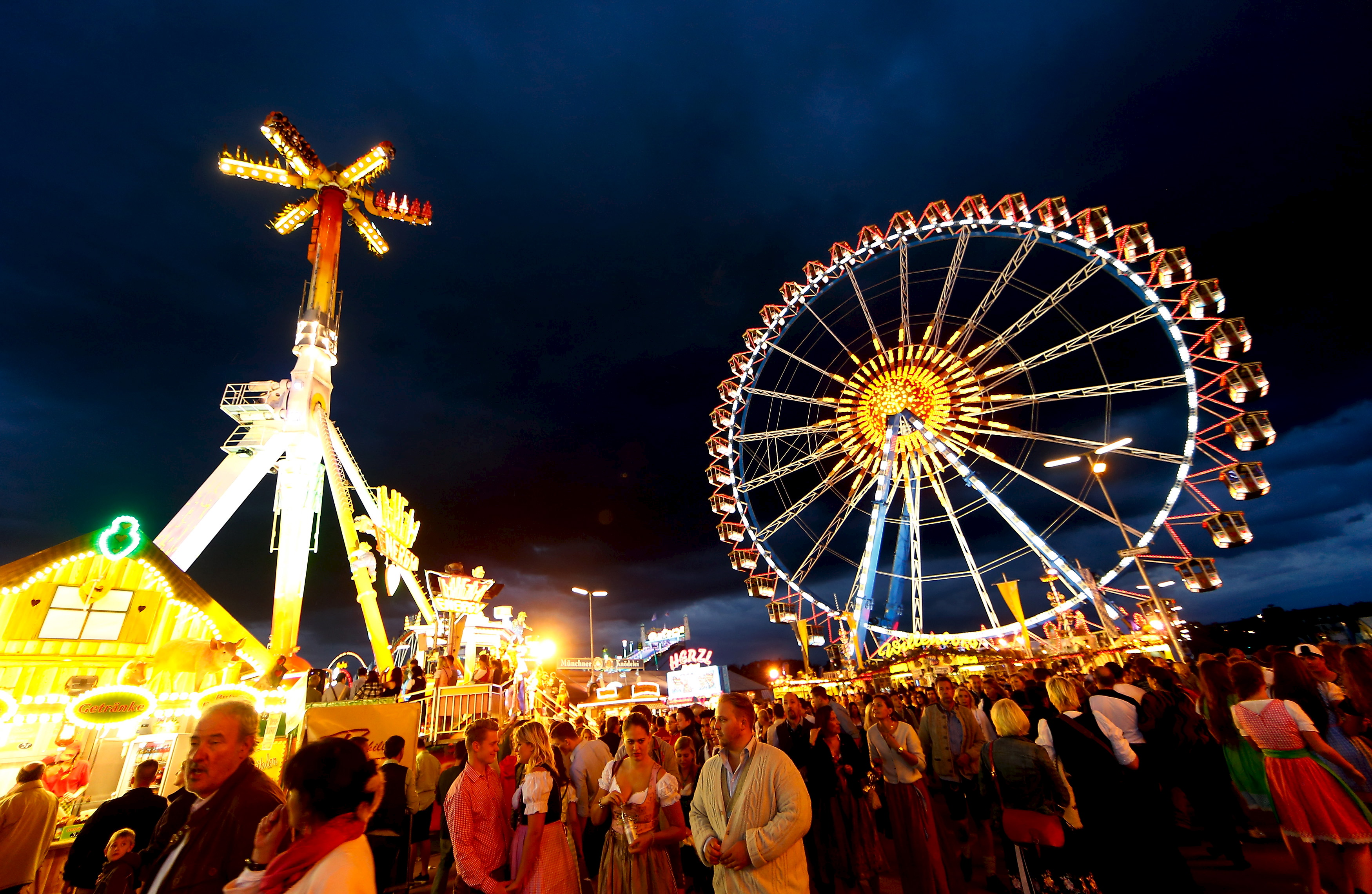 Visitors ride a ferris wheel during the opening day of the 182nd Oktoberfest in Munich, Germany, September 19, 2015. Millions of beer drinkers from around the world will come to the Bavarian capital over the next two weeks for Oktoberfest, which starts today and runs until October 4, 2015. REUTERS/Michael Dalder - RTS1WLR