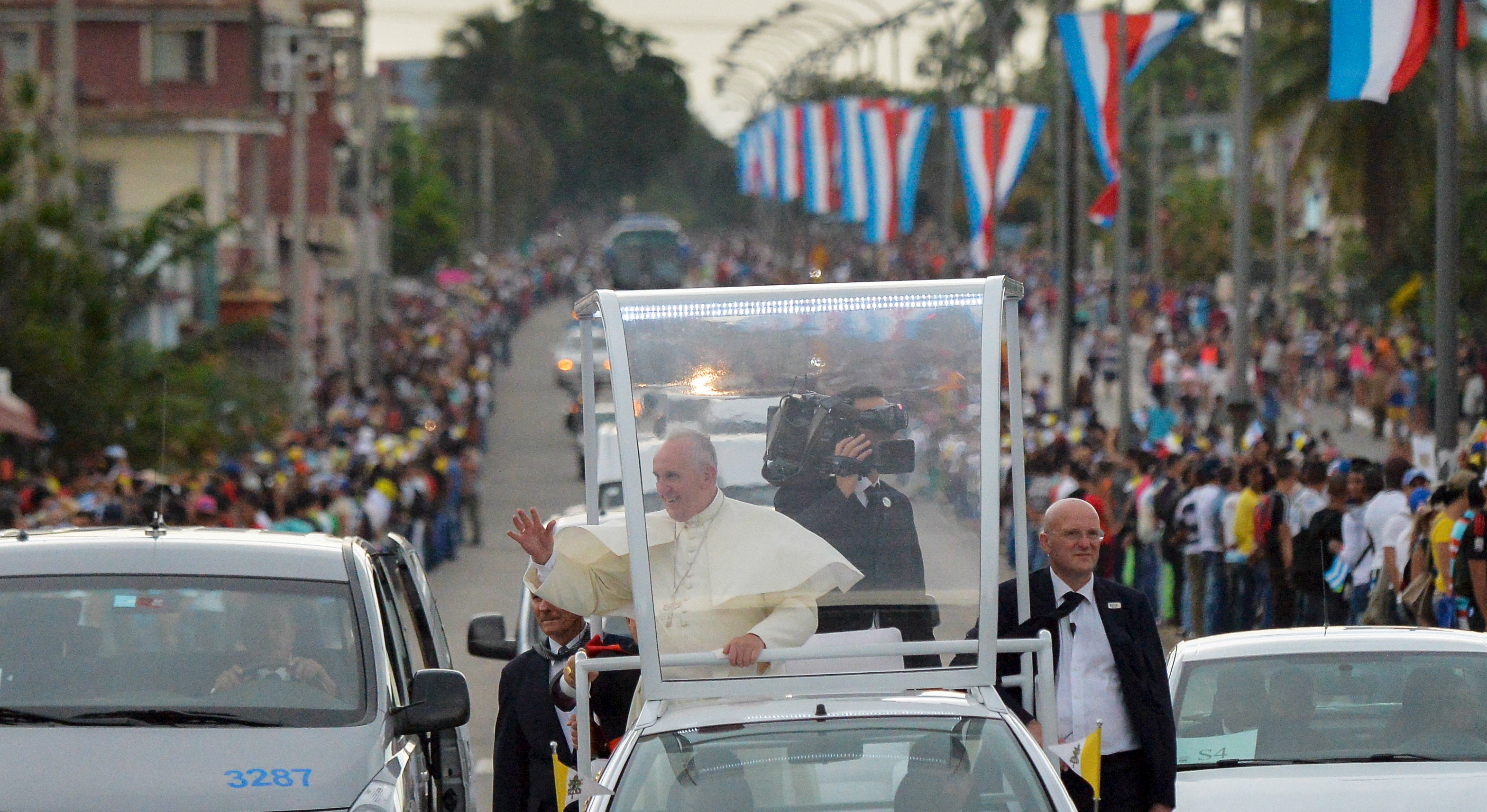 Pope Francis is welcomed by Cubans during his journey from Jose Marti airport to the Nunciature in Havana, on September 19, 2015. Pope Francis' plane landed in Havana on Saturday at the start of a nine-day tour of Cuba and the United States whose recent diplomatic detente he helped broker. REUTERS/Adalberto Roque/Pool??      TPX IMAGES OF THE DAY      - RTS1XND