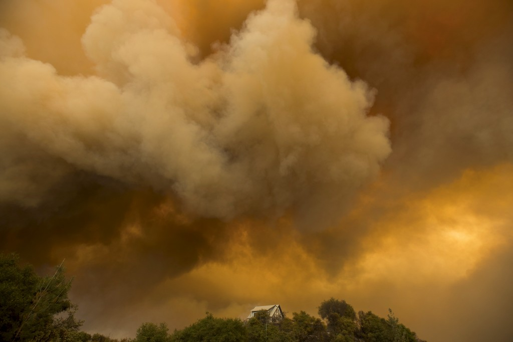 Billowing smoke rises above a residence as the Butte Fire burns in San Andreas, California September 11, 2015. The so-called Butte Fire has destroyed six homes and two outbuildings since it erupted on Wednesday near the former gold mining town of Jackson. Governor Jerry Brown on Friday declared a state of emergency for Amador and Calaveras counties, which were damaged by the blaze.  REUTERS/Noah Berger      TPX IMAGES OF THE DAY      - RTSQ22