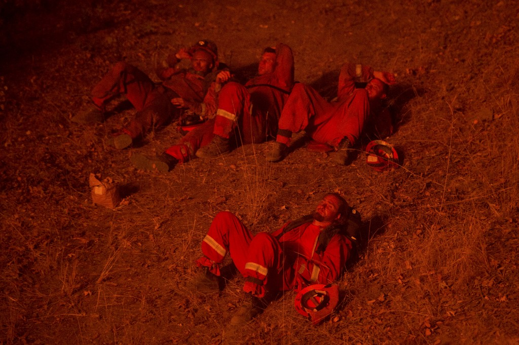 Inmate firefighters, lit by the glow of a backfire, rest while battling the Butte fire near San Andreas, California September 12, 2015. The Butte fire has destroyed 86 homes and 51 outbuildings in rural Amador and Calaveras counties, where it covers an estimated 65,000 acres (26,305 hectares), officials said. REUTERS/Noah Berger - RTSU1J