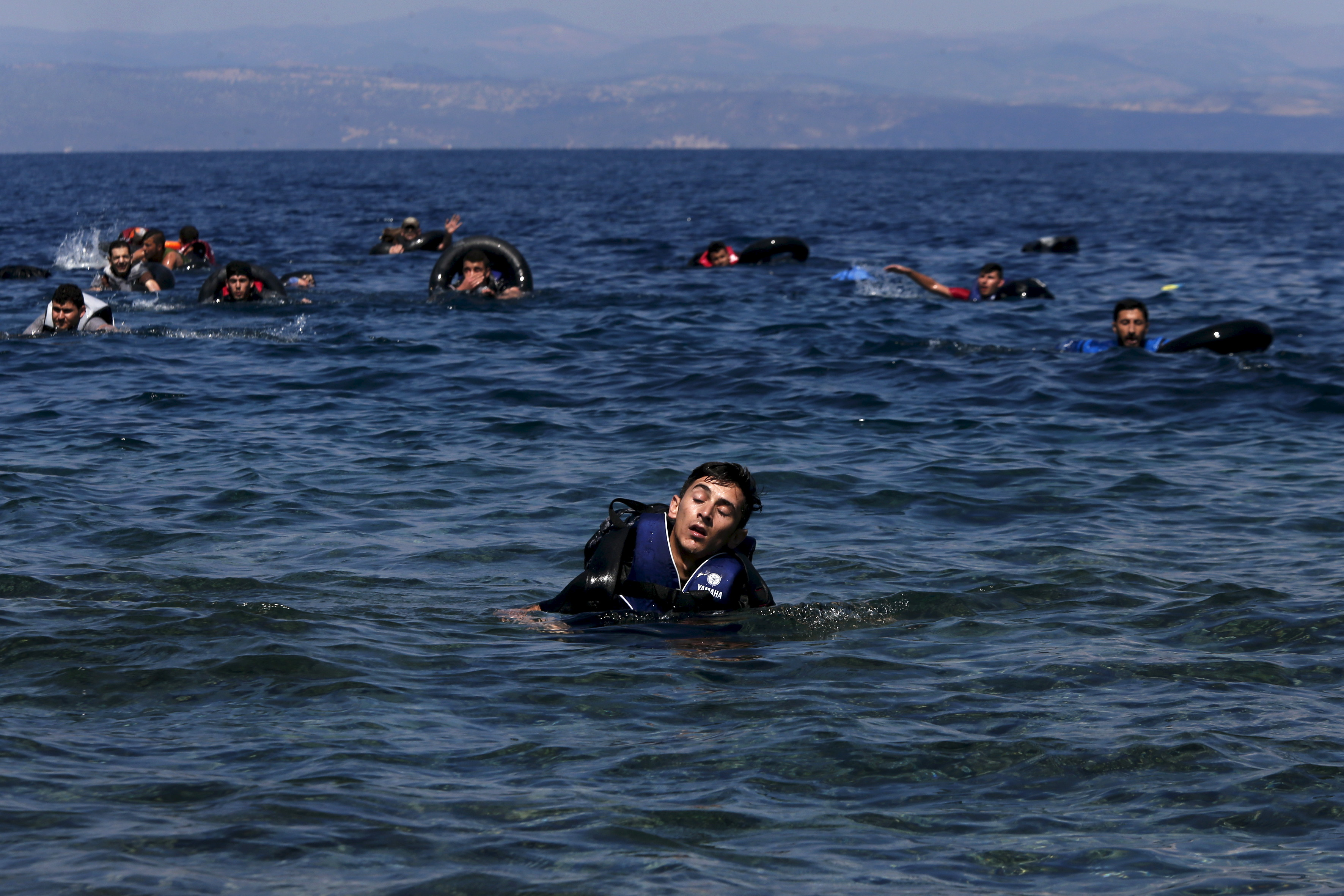 A refugee reacts from exhaustion while swimming towards the shore after a dinghy carrying Syrian and Afghan refugees deflated some 100m away before reaching the Greek island of Lesbos, September 13, 2015. Of the record total of 432,761 refugees and migrants making the perilous journey across the Mediterranean to Europe so far this year, an estimated 309,000 people had arrived by sea in Greece, the International Organization for Migration (IMO) said on Friday. About half of those crossing the Mediterranean are Syrians fleeing civil war, according to the United Nations refugee agency. Photo by Alkis Konstantinidis/Reuters