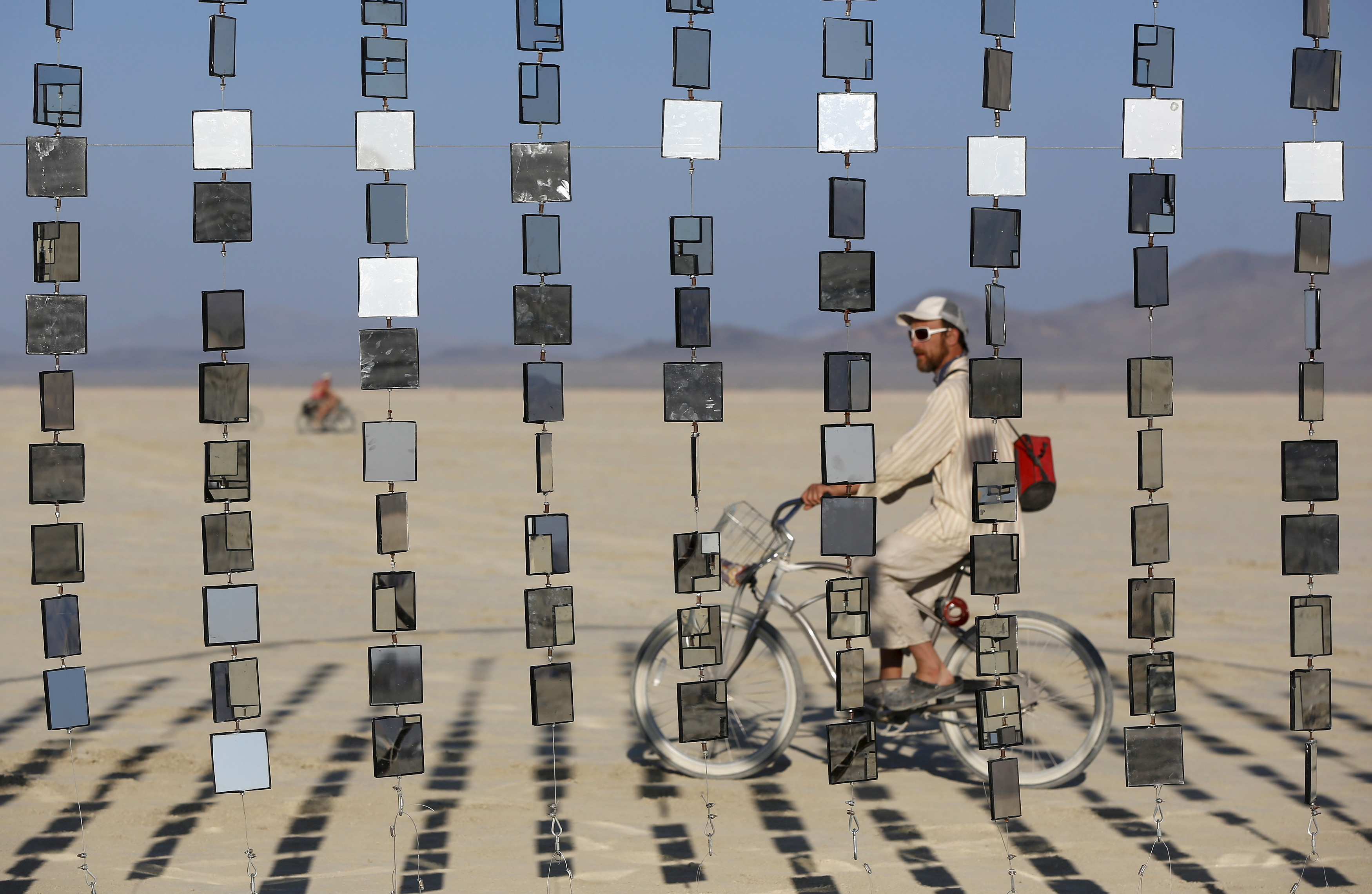 "A man rides by an art installation at the Burning Man 2015 ""Carnival of Mirrors"" festival on Aug. 31. The event's first legal permit came from the Bureau of Land Management in 1991. Photo by Jim Urquhart/Reuters"