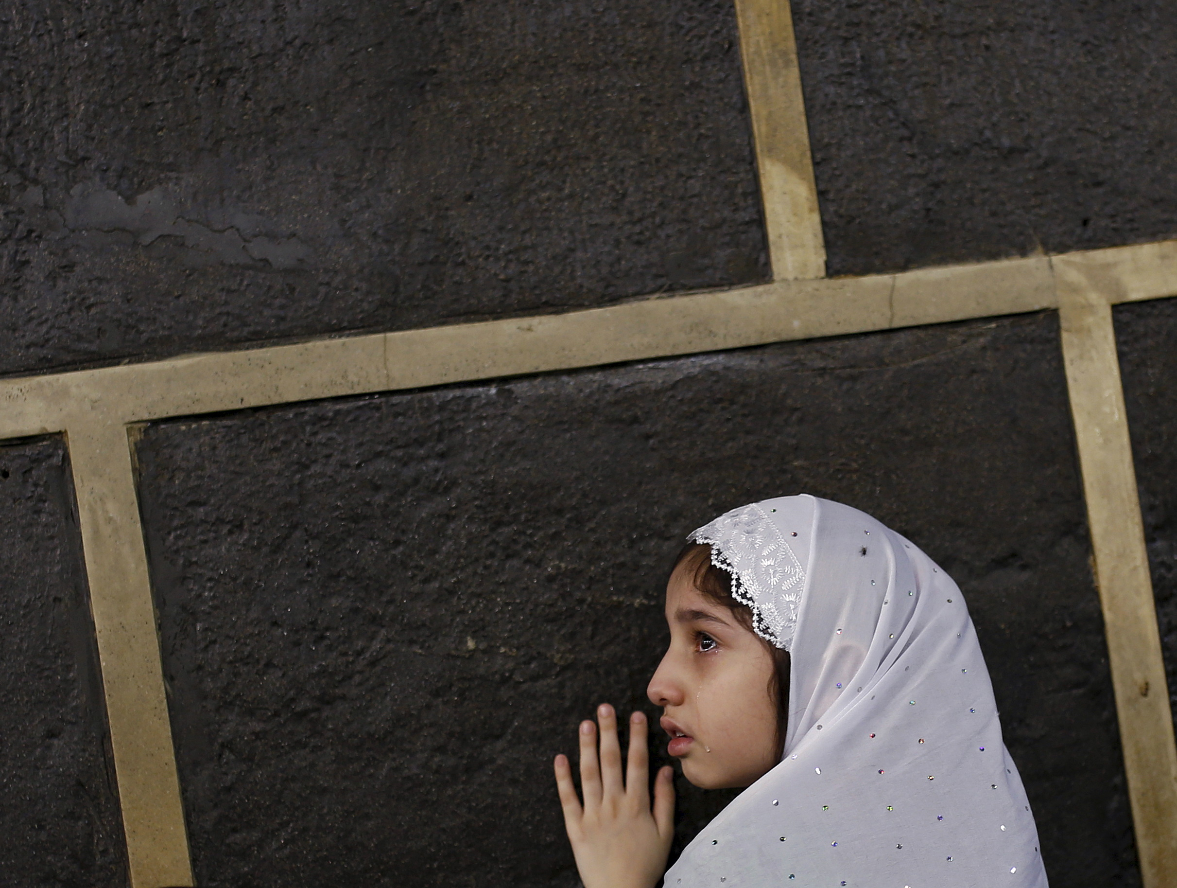 A Muslim girl touches the holy Kaaba at the Grand Mosque on the first day of Eid al-Adha  during the annual hajj pilgrimage in Mecca in Saudi Arabia on Sept. 24. Photo by Ahmad Masood/Reuters