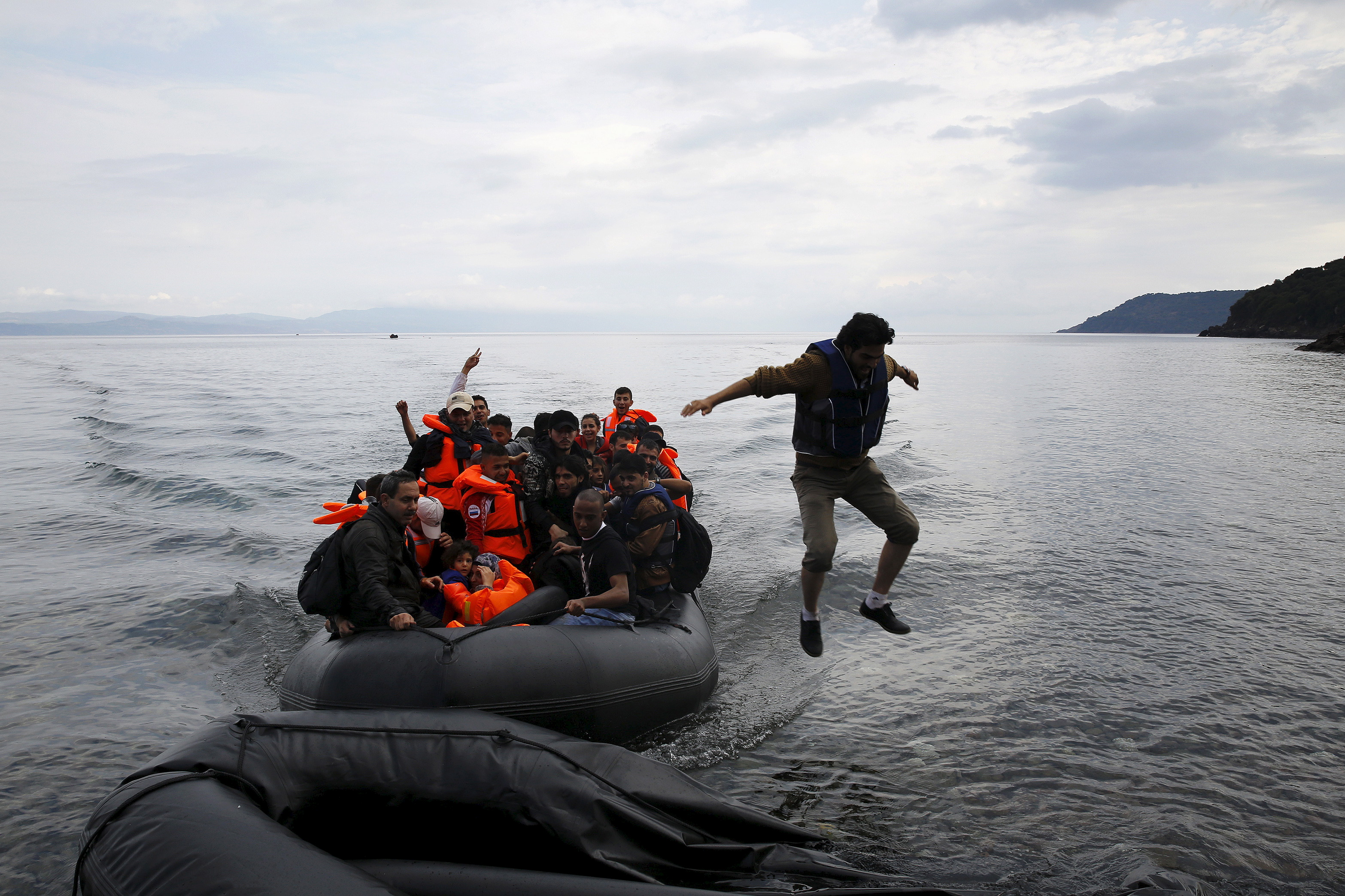 A migrant jumps off an overcrowded dinghy upon arriving in the Greek island of Lesbos, after crossing a part of the Aegean Sea from Turkey to Lesbos September 24, 2015.  REUTERS/Yannis Behrakis  - RTX1S91V