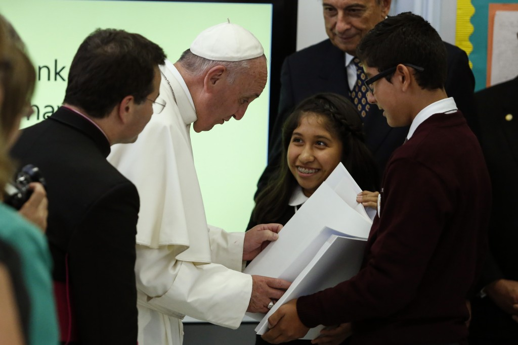 Pope Francis receives a book from Shaila Cuellar (center) and Victor Franco (right) while visiting a classroom in Our Lady Queen of Angels School in East Harlem in New York on Sept. 25. Photo by Kena Betancur/AFP/Pool via Reuters