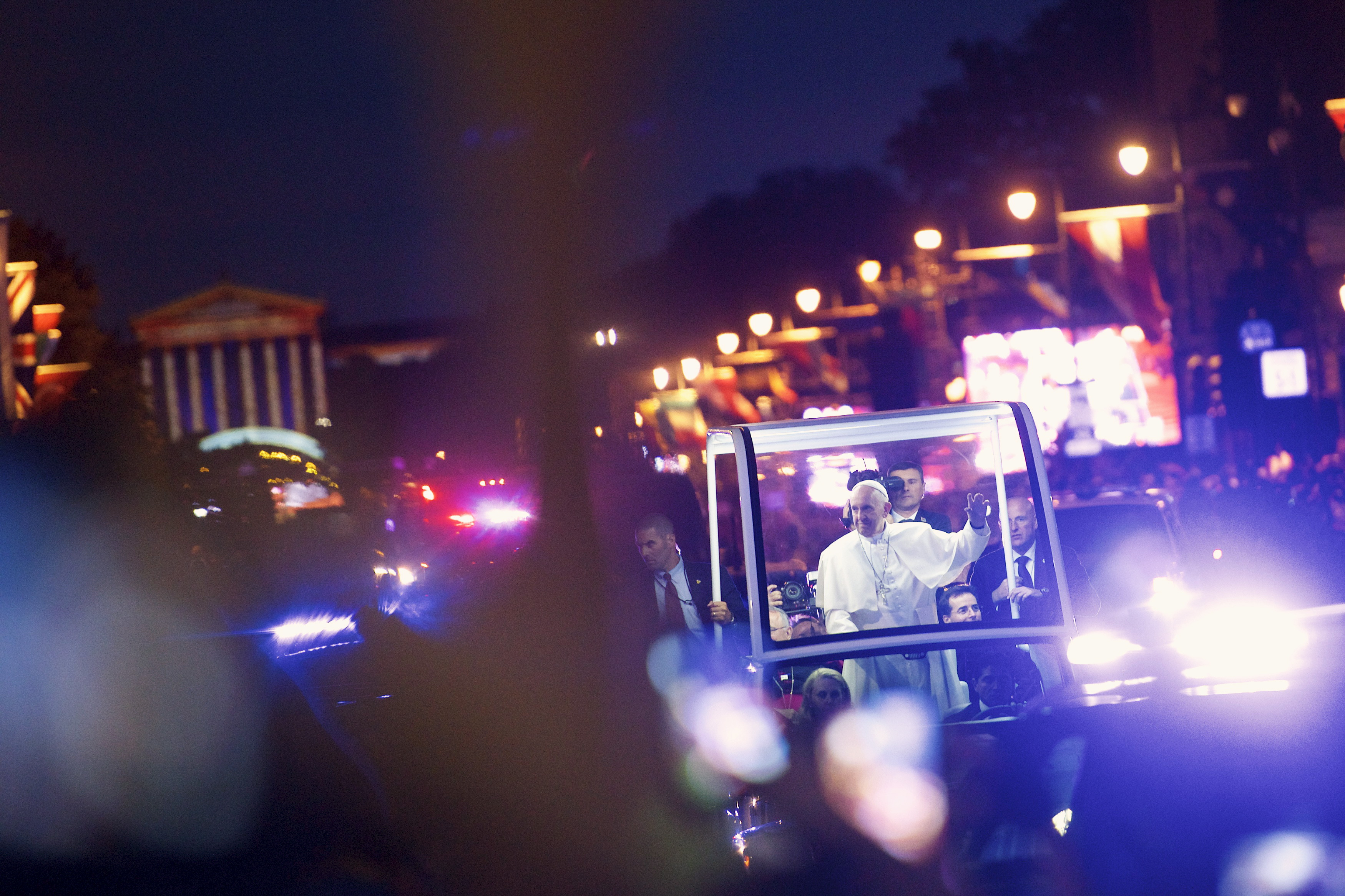 Pope Francis waves to the crowd on the Benjamin Franklin Parkway before the Festival of Families evening program in Philadelphia, Pennsylvania, September 26, 2015. Pope Francis, speaking in America's birthplace on Saturday, offered stout words of support to Hispanic and other immigrants in the United States, telling them not to be discouraged at a time when some prominent politicians are directing hostility toward them. REUTERS/Mark Makela - RTX1SNIR