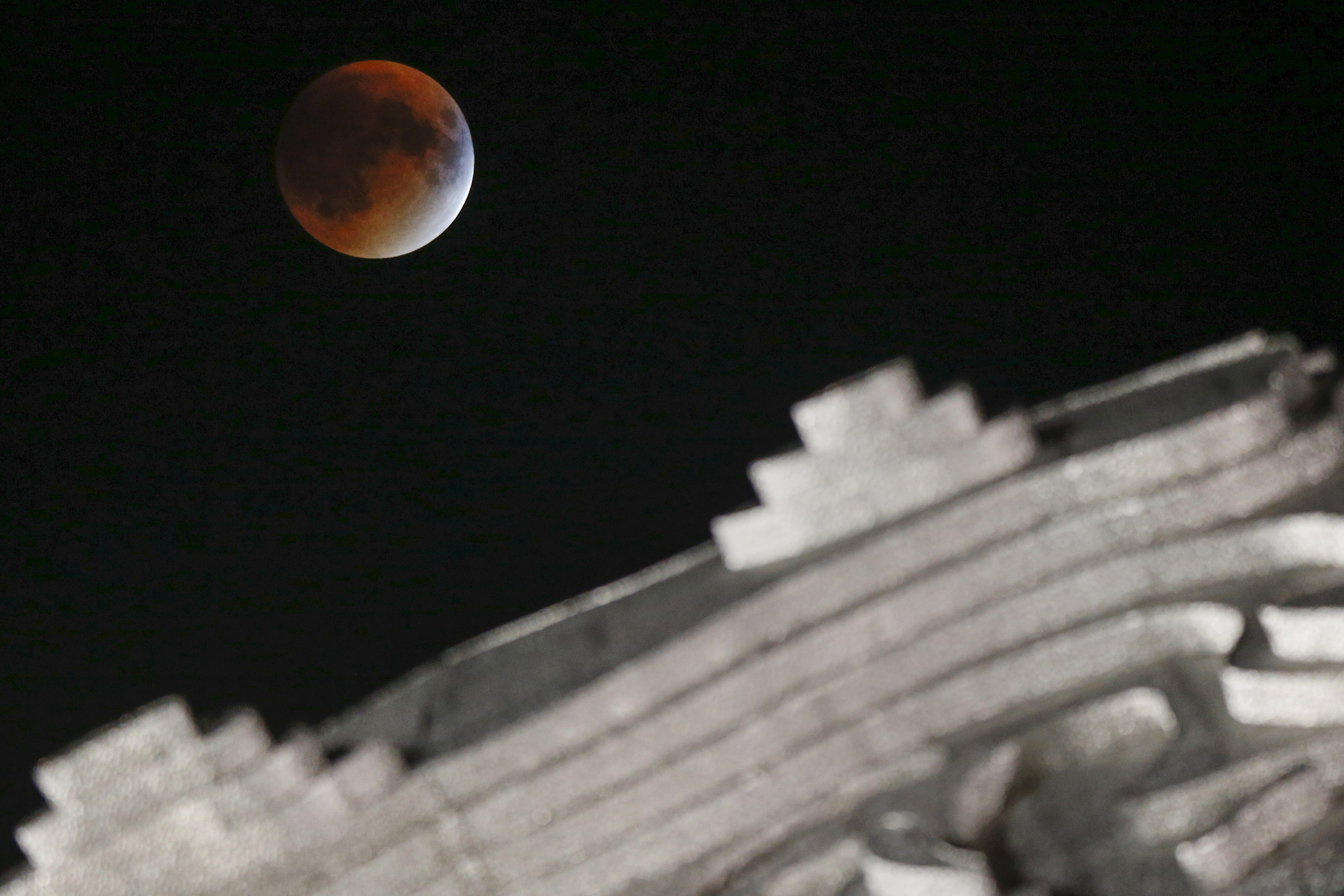 "A supermoon is seen over the Unisphere at Flushing Meadows Corona Park in the Queens borough of New York on Sept. 27. The total ""supermoon"" lunar eclipse is also known as a ""blood moon."" Photo by Shannon Stapleton/Reuters"