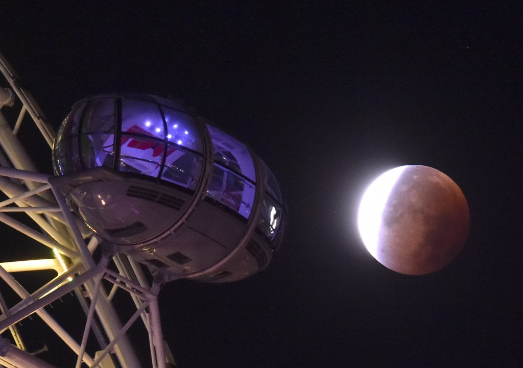 A supermoon is seen during a lunar eclipse behind pods of the London Eye wheel on Sept. 28, 2015. Photo by Toby Melville/Reuters