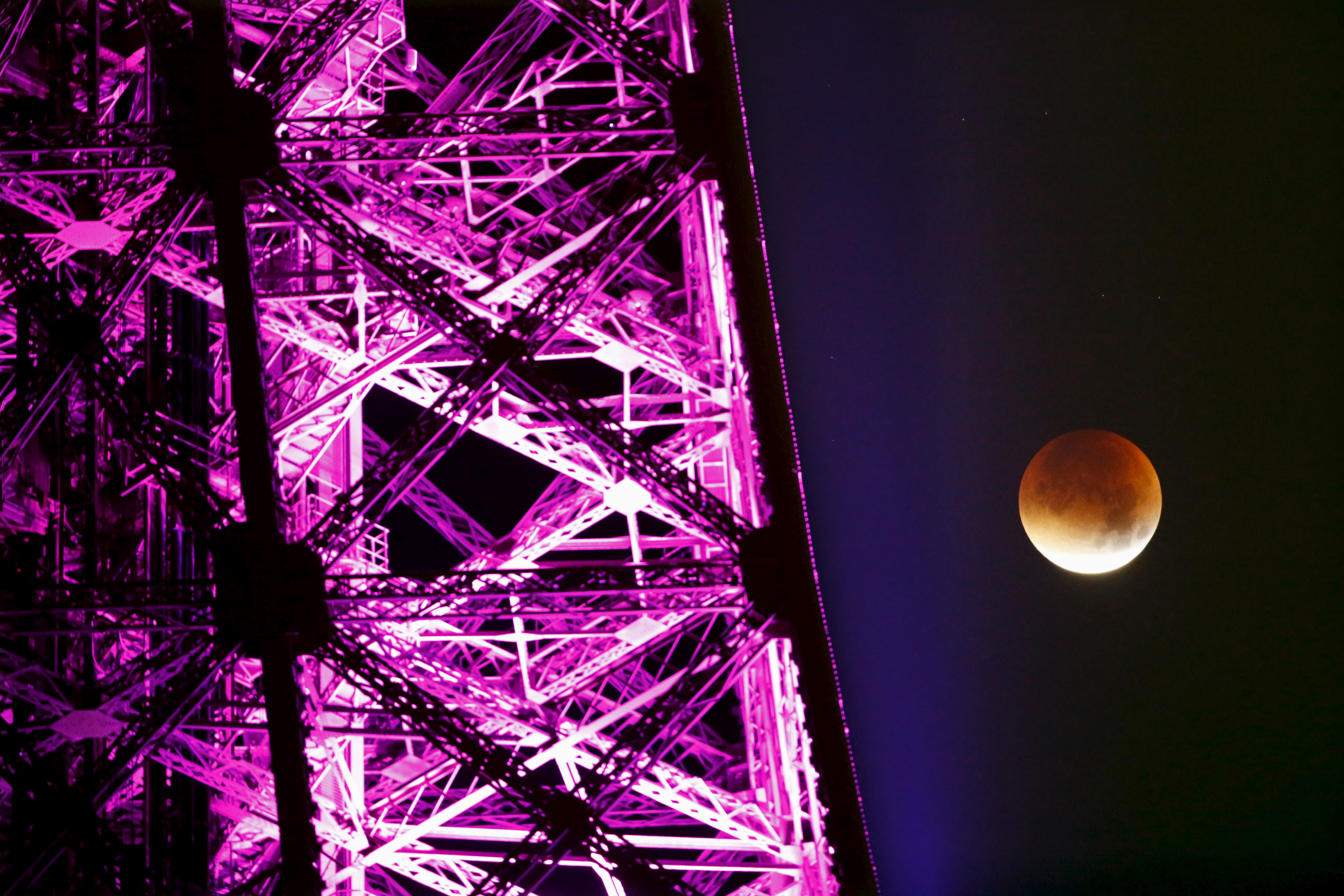 "The ""blood moon"" rises next to a brightly lit Eiffel Tower in Paris, France on Sept. 28. Photo by Charles Platiau/Reuters"