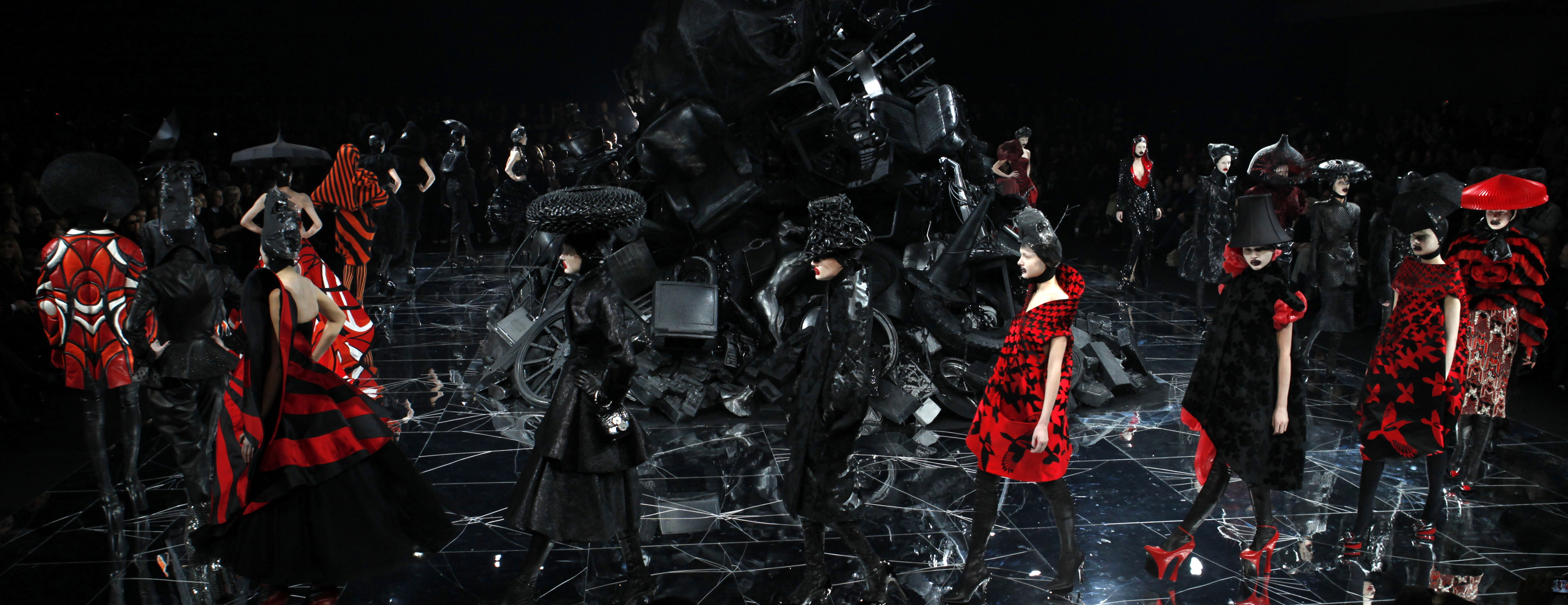 "Models present creations by British designer Alexander McQueen as part of his ""Horn of Plenty"" ready-to-wear women's collection during Paris Fashion Week on March 10, 2009. In the middle of the runway is a pile of garbage, including recycled props from past McQueen shows. Photo by Pascal Rossignol/Reuters"