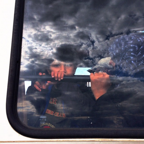 A Syrian boy looks out a bus window as he leaves with his family from the overcrowded field in Roszke, Hungary, to another processing center. People waited in line for hours for these few buses to come. When people got fed up, huge numbers broke through police lines to escape into nearby cornfields earlier today. Even as these people left, more migrants continued to pour over the border from Serbia, just a few hundred yards away. Reportedly, as crowds continued to swell this evening and more tried to leave, Hungarian police pepper-sprayed the migrants to force them to stop. Photo by William Brangham