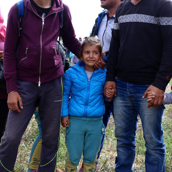 This refugee family joined a larger group of migrants who broke through police barriers in the field where they were being kept in Roszke, Hungary, on the Serbian border. After breaking past the police, the migrants ran on foot heading north across Hungary with hopes of reaching western European countries. Photo by Saskia de Melker.