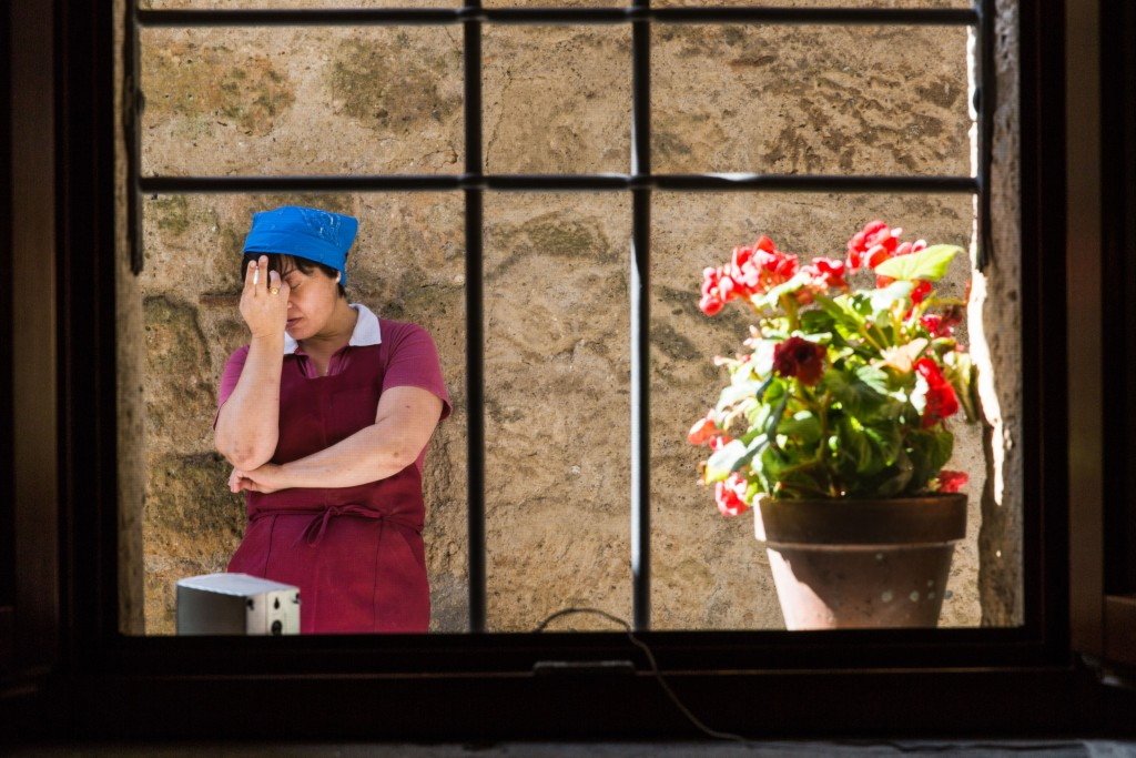 A worker takes a cigarette break outside the Alma Civita restaurant. Photo by Frank Carlson