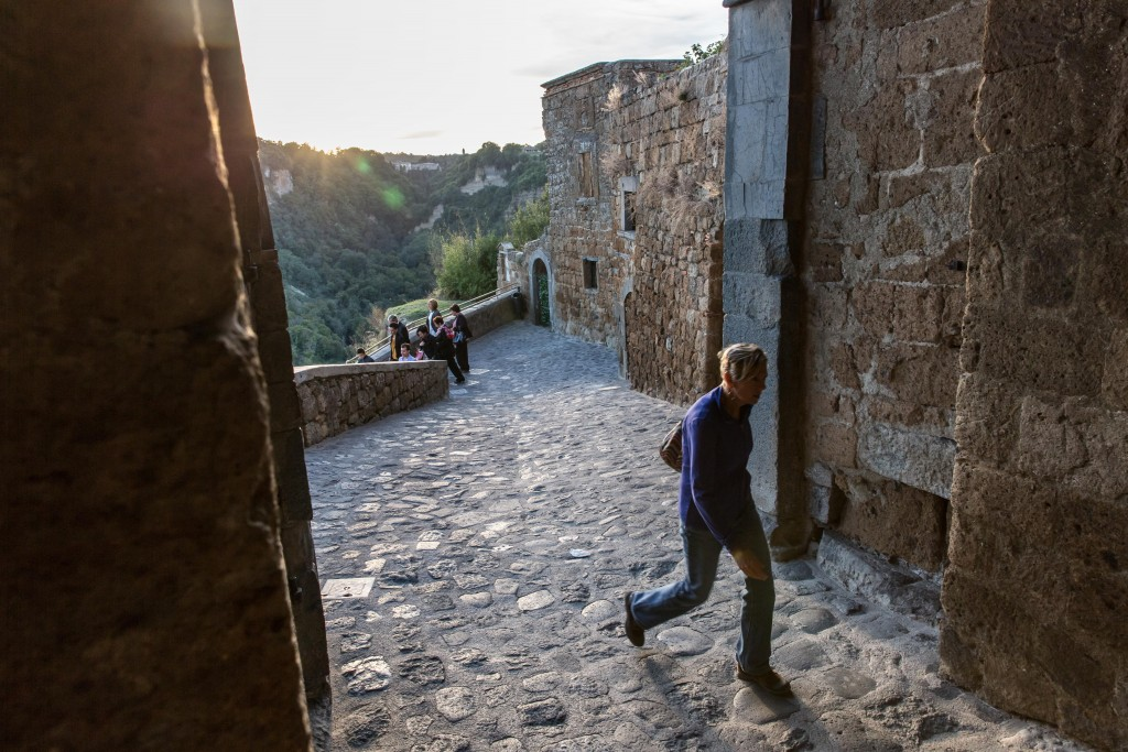 Sunlight fades as a woman enters Civita di Bagnorio from the footbridge as others leave for the day. Photo by Frank Carlson