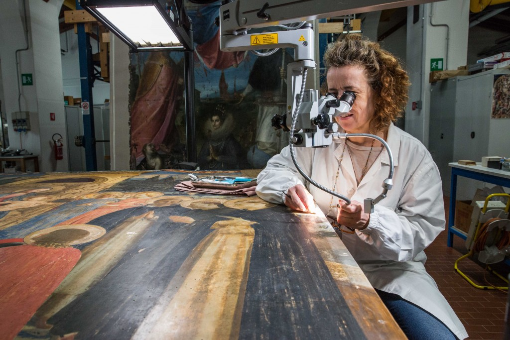 """Caterina Toso cleans the """"San Marco Altarpiece,"""" also known as """"Madonna and the Saints,"""" a painting on wood typically found in the Museum of San Marco in Florence. Commissioned by Cosimo di Medici, it was completed by Fra Angelico in the mid-15th century. Photo by Frank Carlson"""