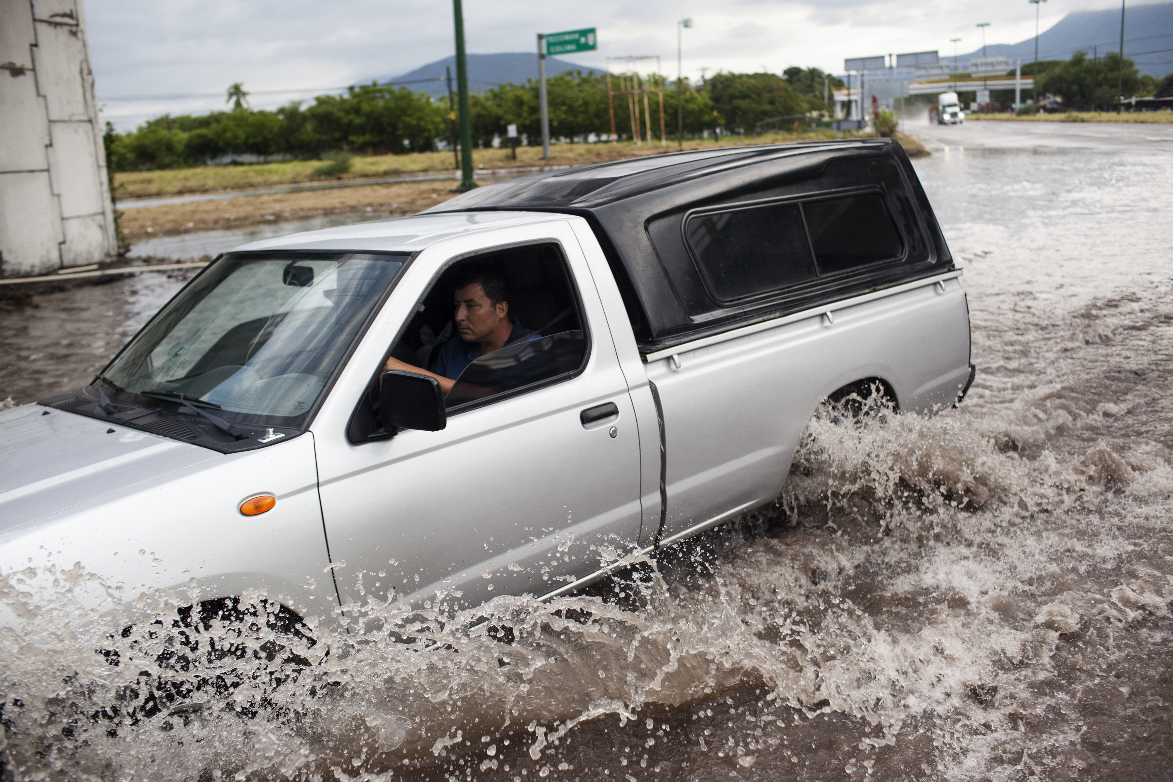 TECOMAN MX - OCTOBER 24: A truck drives through a flooded out turn off at the entrance to the city after heavy flooding from Hurriane Patricia October 24, 2015 in Tecoman, Colima, Mexico. Hurricane Patricia struck Mexico's West coast as the most powerful storm ever recorded in the Western Hemisphere but rapidly lost energy as it moved inland.  (Photo by Brett Gundlock/Getty Images)