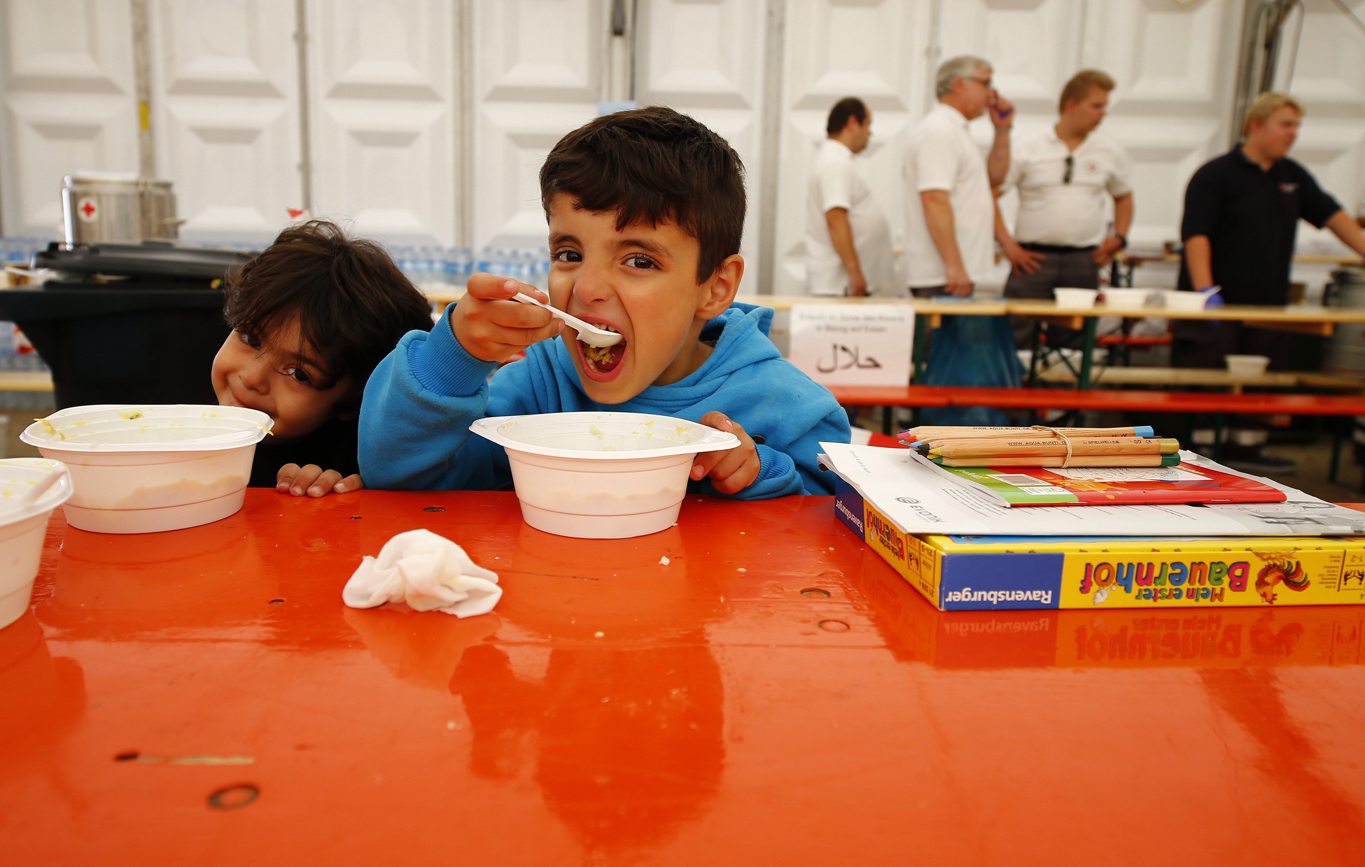 A child eats at a temporary shelter in a sports hall in Hanau, Germany, on Sept. 18, 2015. Photo by Kai Pfaffenbach/Reuters