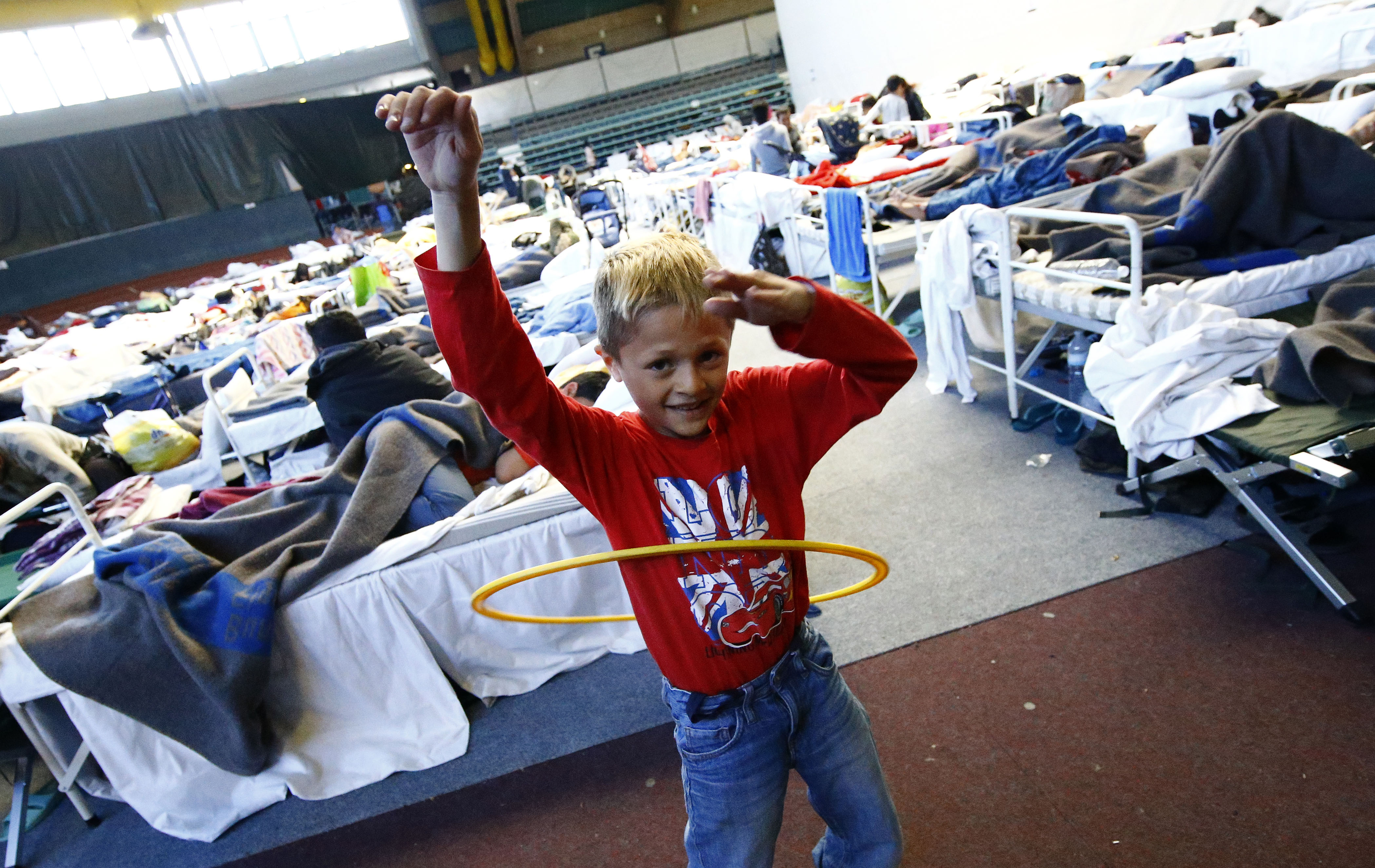 A child plays with a hoola hoop at a temporary shelter in a sports hall in Hanau, Germany, on Oct. 1, 2015. Photo by Kai Pfaffenbach/Reuters